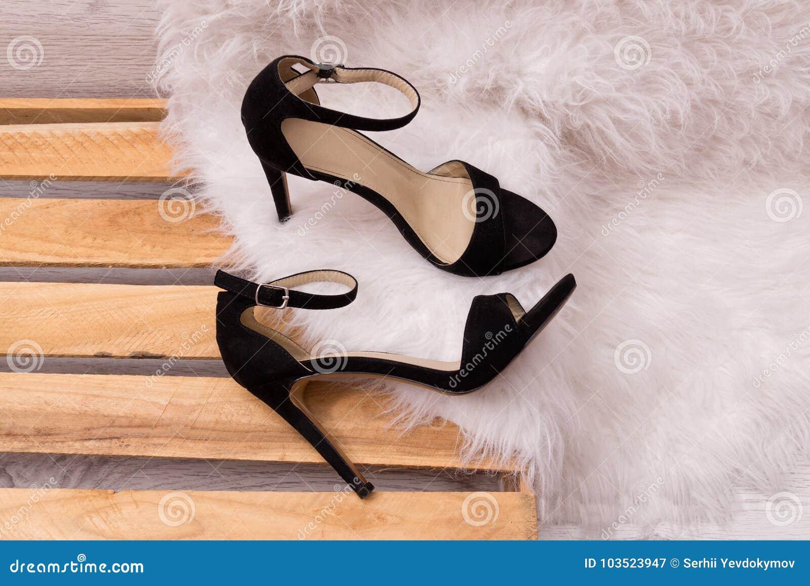 Concepto de la manera Bolso femenino negro, suéter caliente en una parte posterior de madera