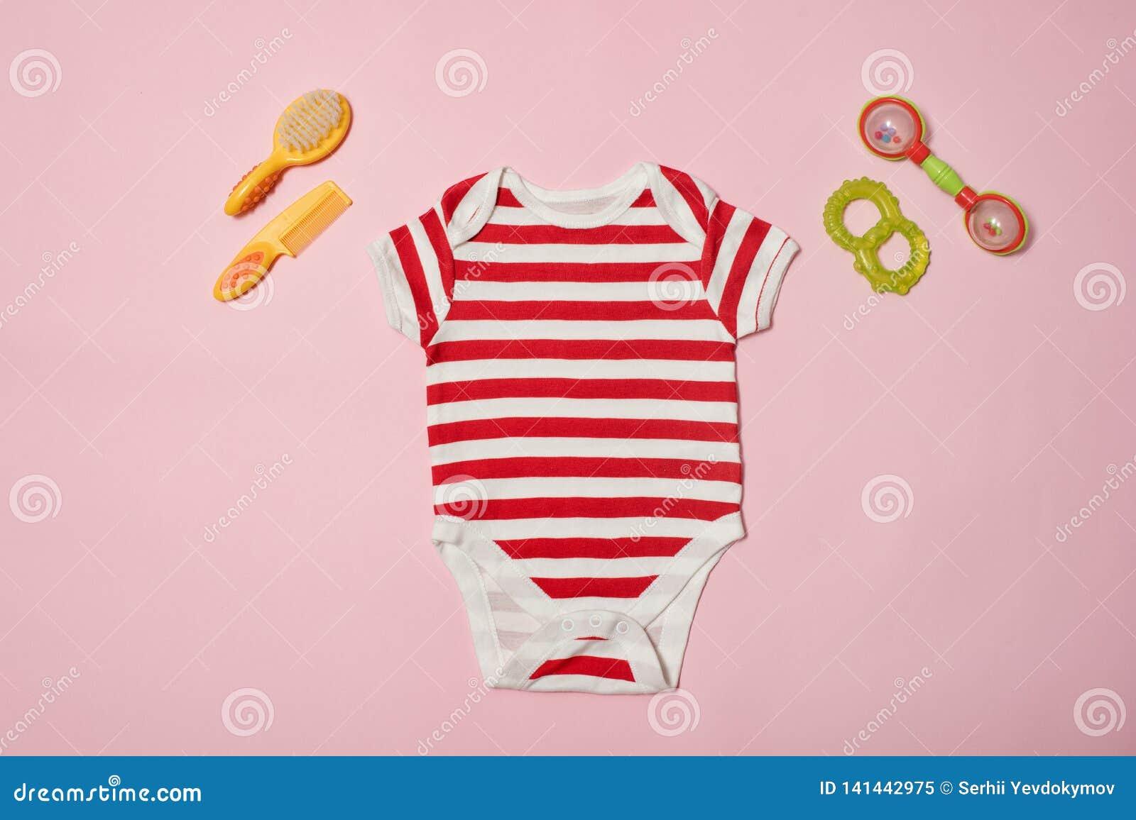 Concepto de la moda del bebé en un fondo rosado Mono, concha de peregrino y beanbag rayados