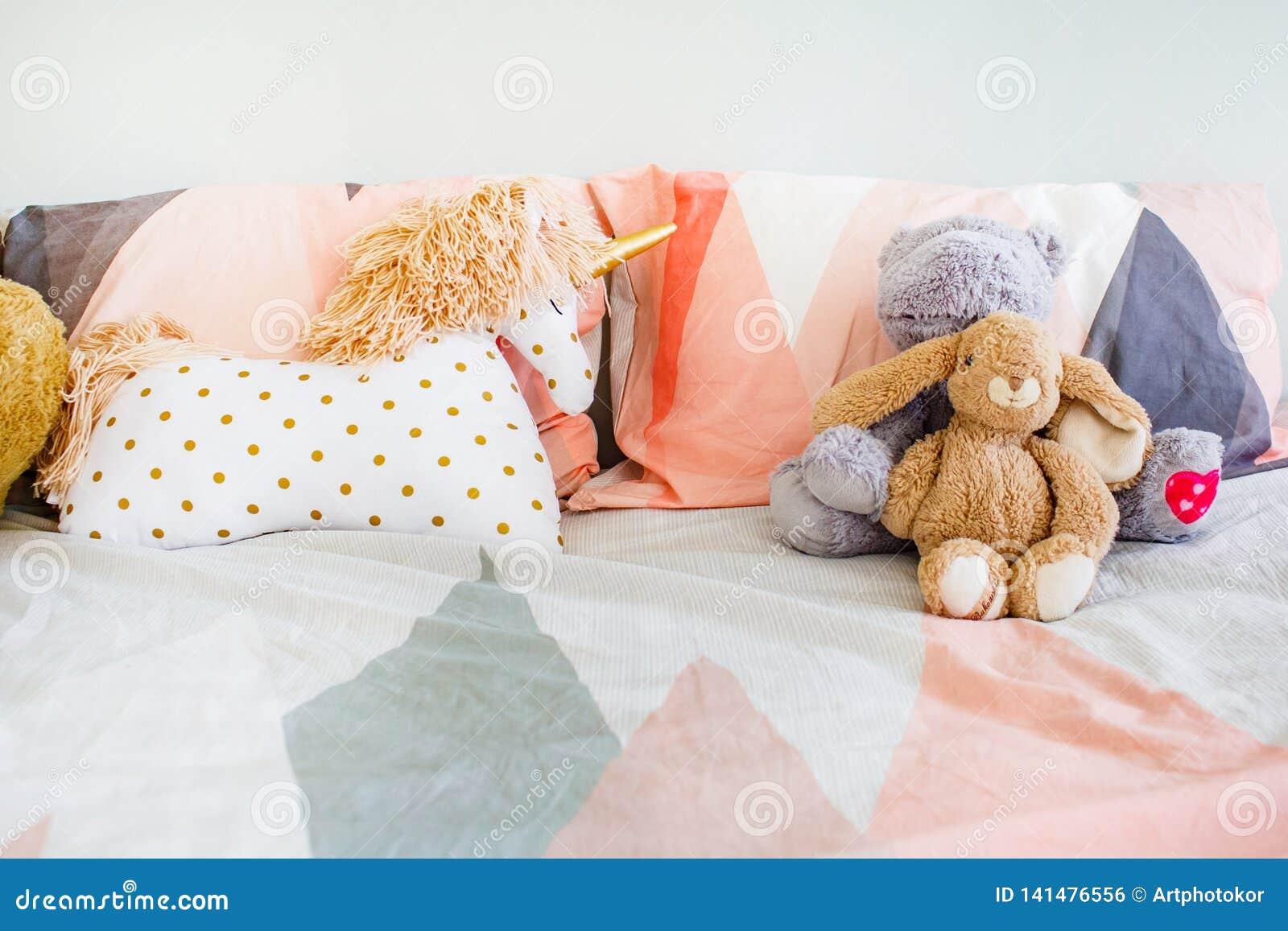 Concepto de la niñez Juguetes puestos en ropa de cama en primer del sitio durmiente