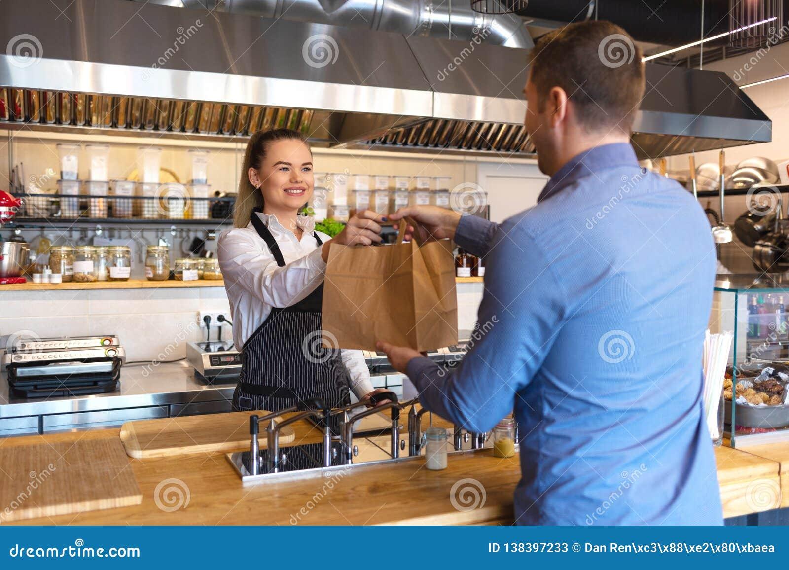 Concepto de la pequeña empresa y del empresario con la camarera joven sonriente que lleva al cliente negro de la porción del dela