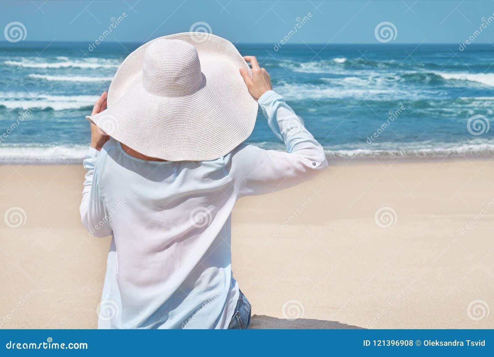Concepto de la playa del verano Mujer en sombrero grande en la playa idílica Arena blanca, cielo azul y mar del cristal