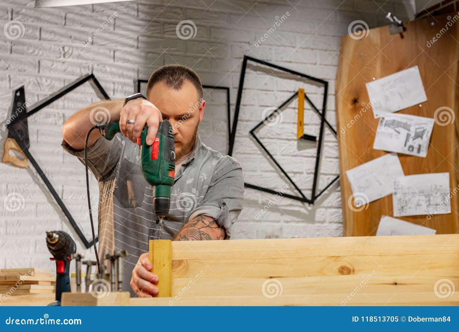 Concepto de la profesión, de la carpintería, de la artesanía en madera y de la gente - carpintero con el tablón de madera de la p