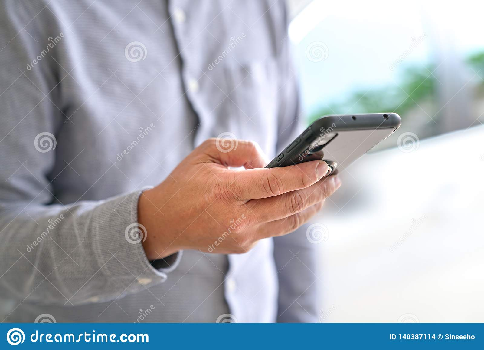 Concepto de la tecnología: Hombre de negocios que hojea o que practica surf el teléfono móvil