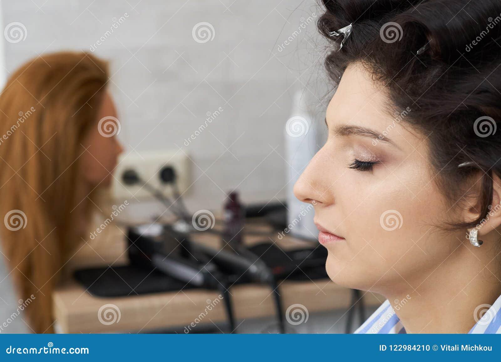 Concepto de moda y de belleza La morenita hermosa con el pelo enorme se preparó para el trabajo de un estilista