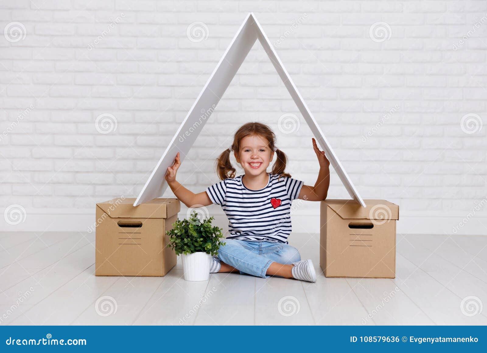 Concepto de mudanza y de vivienda muchacha feliz del niño con las cajas