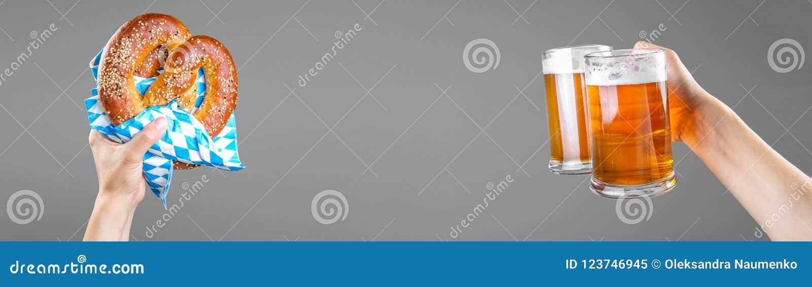 Concepto de Oktoberfest - manos que sostienen la cerveza y el pretzel