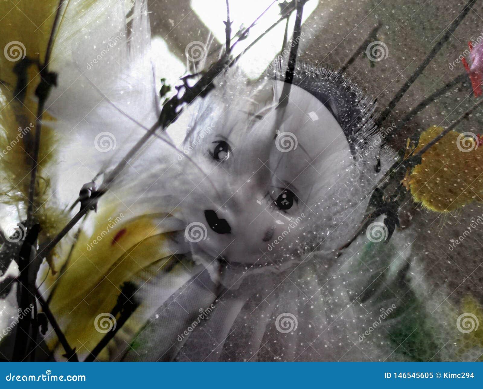 Concepto de Pascua Una muñeca triste de la porcelana del pierrot entre las ramitas y las plumas