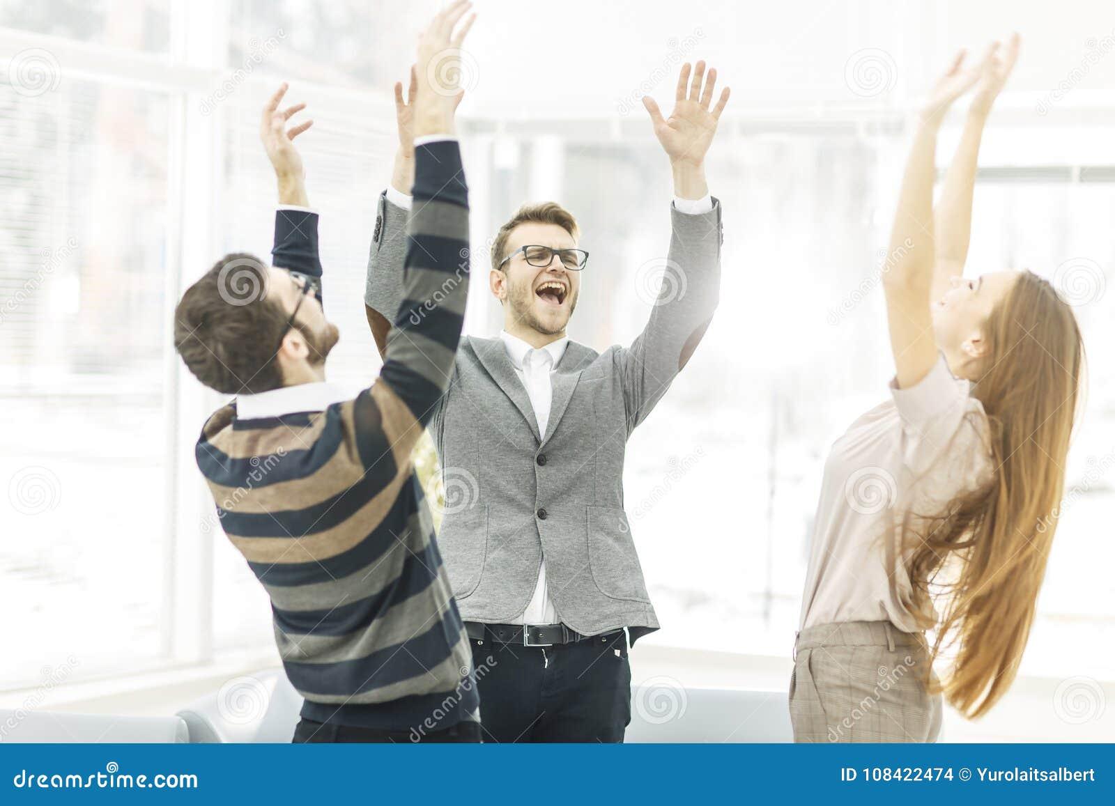 Concepto de victoria - el equipo jubiloso del negocio que se coloca en un círculo, manos para arriba en disfruta éxito