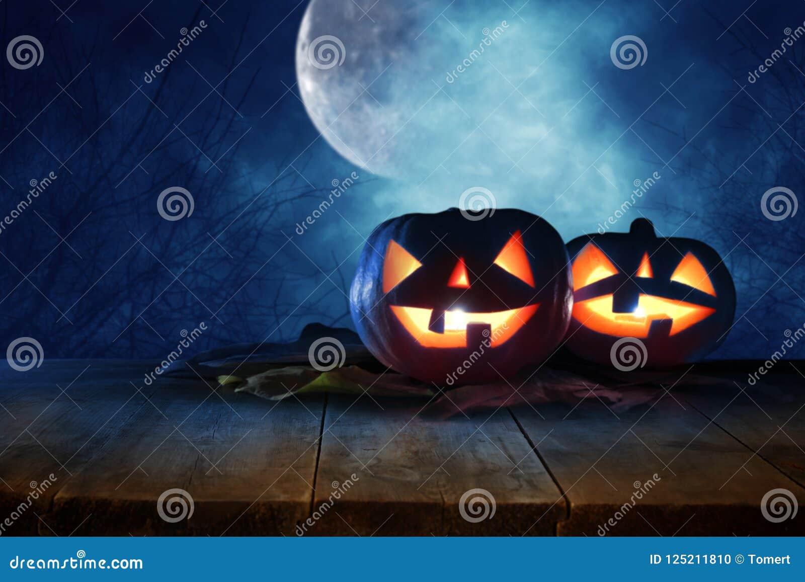 Concepto del día de fiesta de Halloween Tabla rústica vacía delante de las calabazas sobre la tabla de madera en el bosque asusta