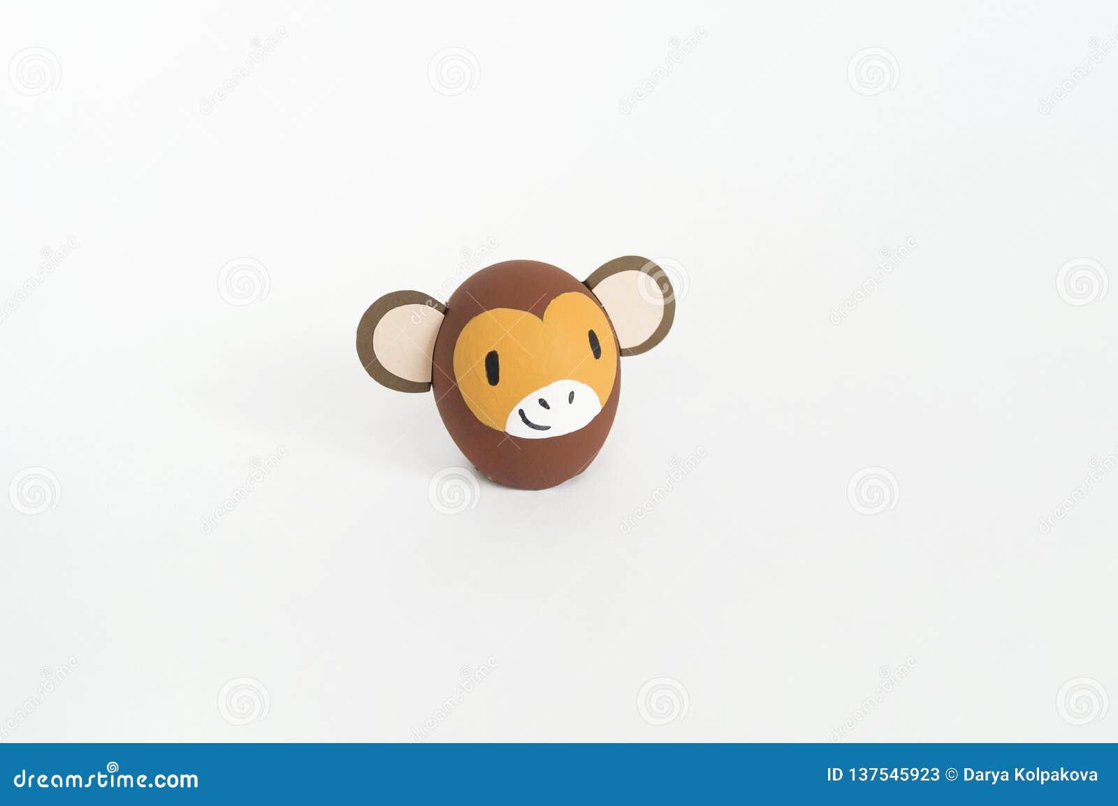 Concepto del día de fiesta de Pascua con los huevos hechos a mano lindos: mono marrón