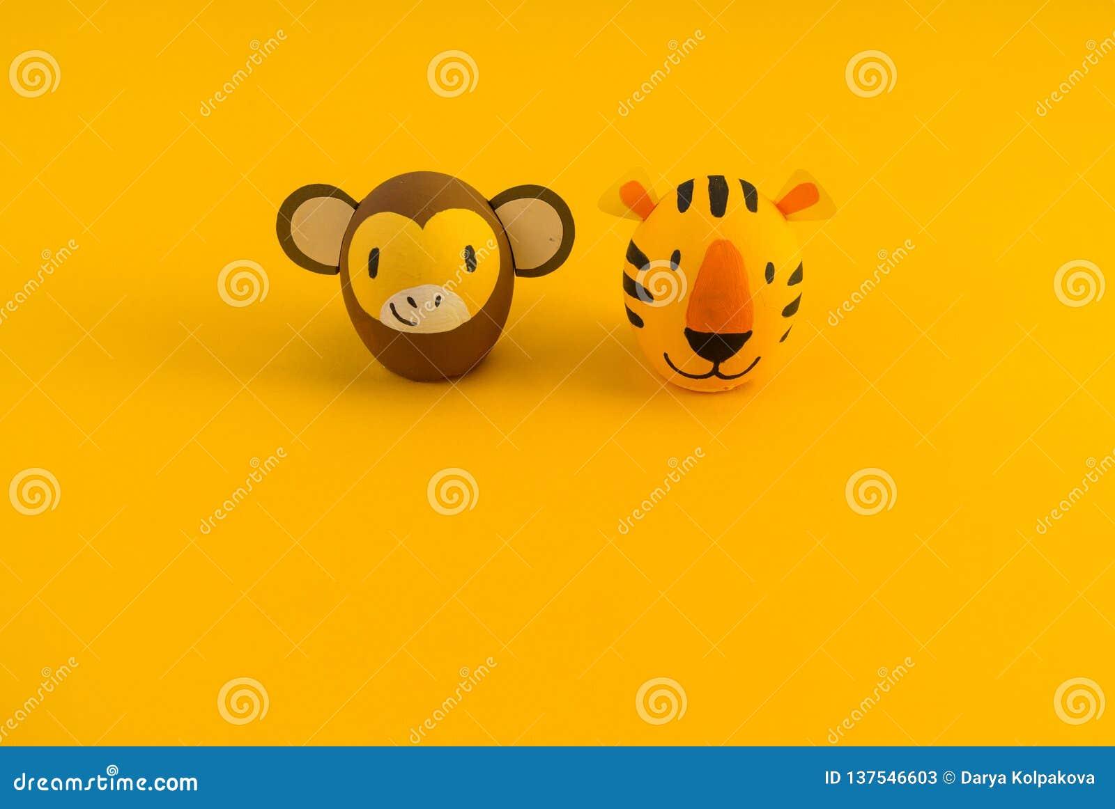 Concepto del día de fiesta de Pascua con los huevos hechos a mano lindos: tigre y mono anaranjados