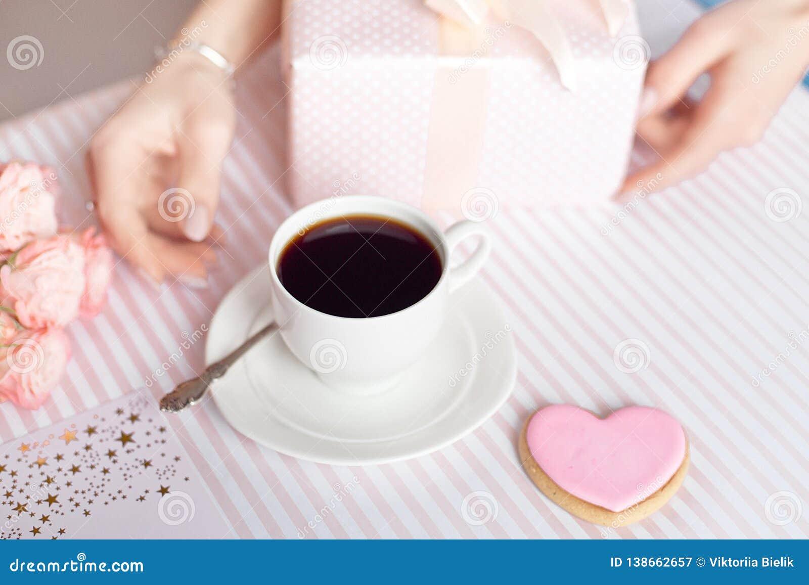 Concepto del día de madre - un regalo para las manos de las mujeres con una taza blanca de café y de rosas Copie el espacio