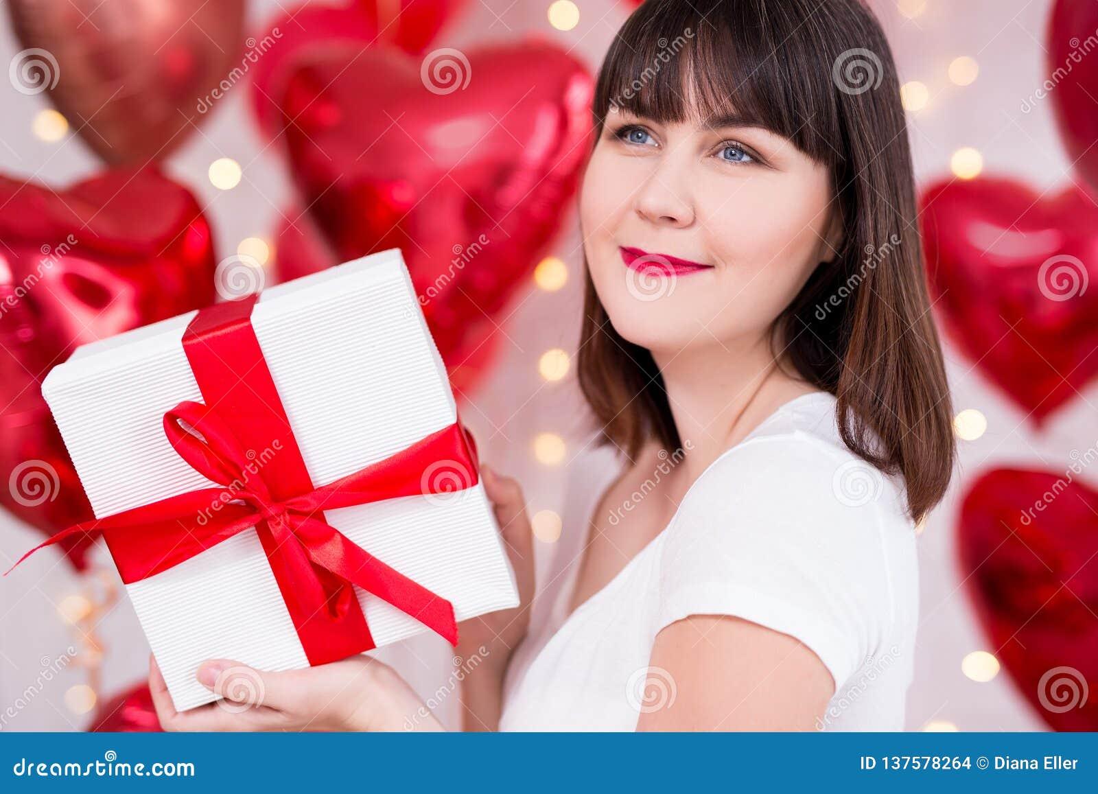 Concepto del día de tarjeta del día de San Valentín - cierre encima del retrato de la mujer de sueño feliz con la caja de regalo
