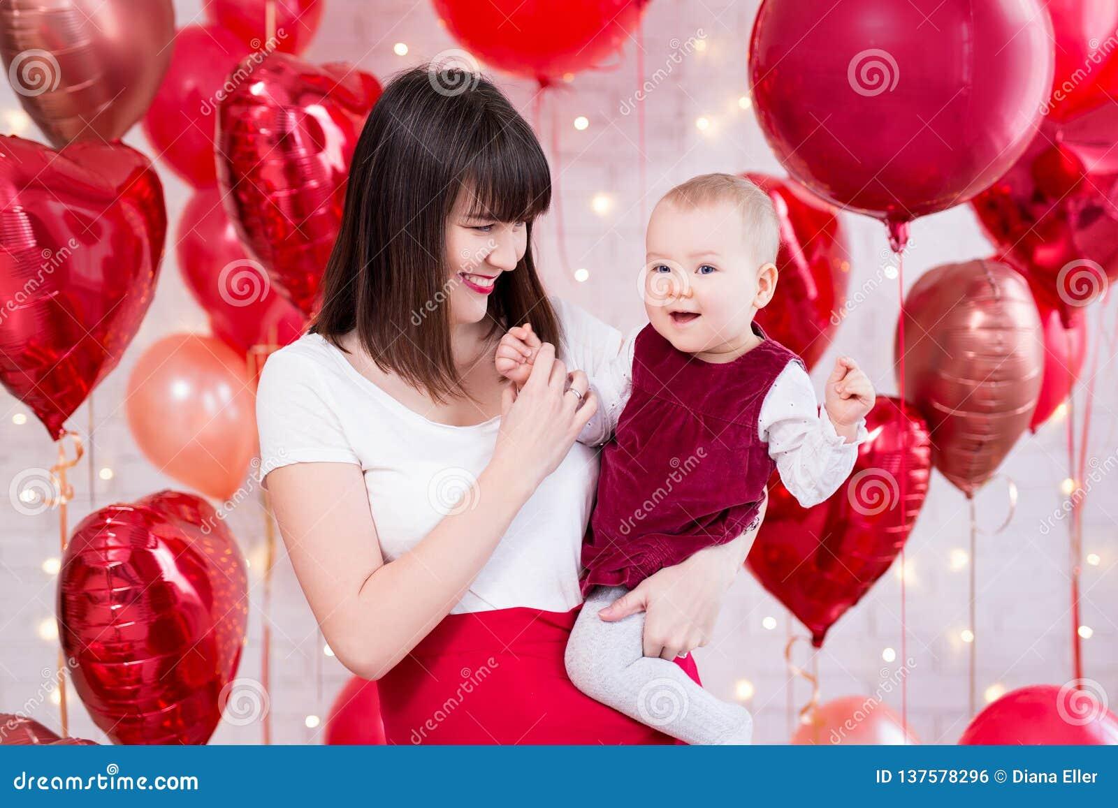 Concepto del día de tarjeta del día de San Valentín - mujer hermosa feliz con la hija sobre fondo rojo de los globos