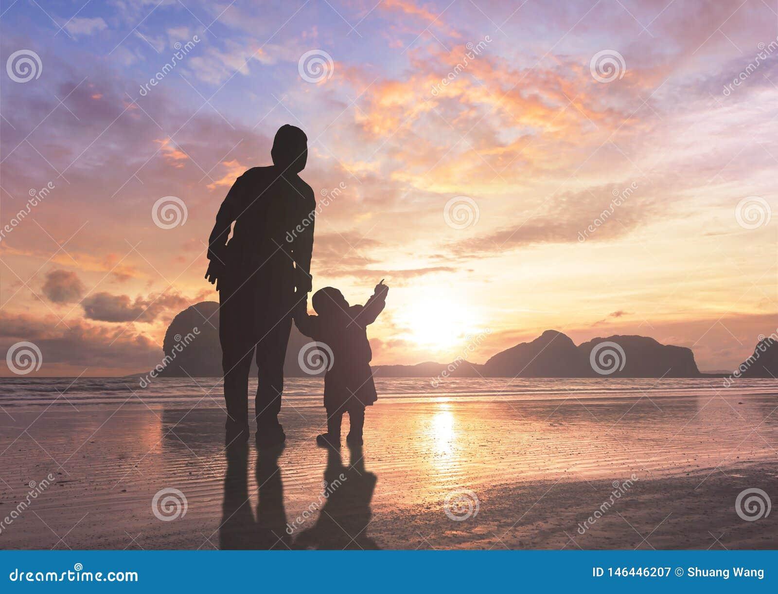 Concepto del d?a de madre: mam? y ni?o en fondo de la puesta del sol