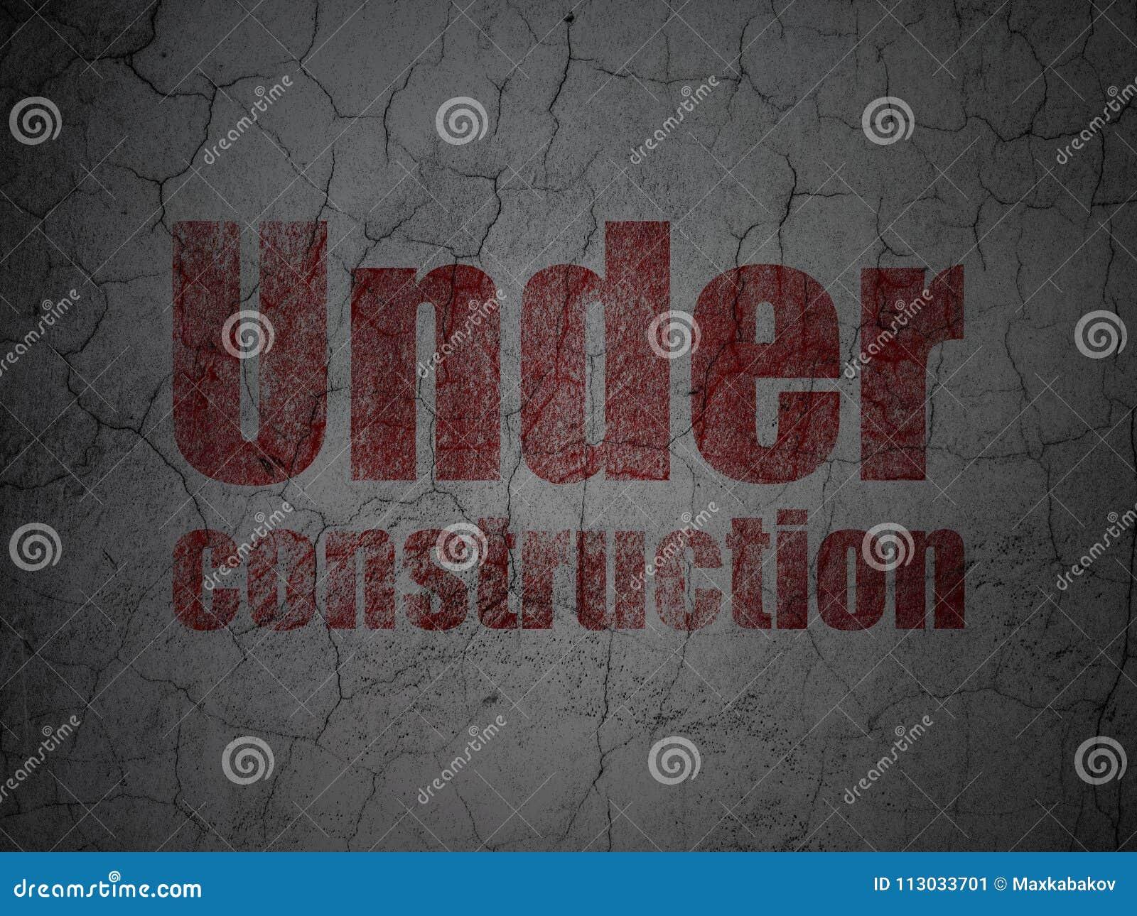 Concepto del diseño web: Bajo construcción en fondo de la pared del grunge