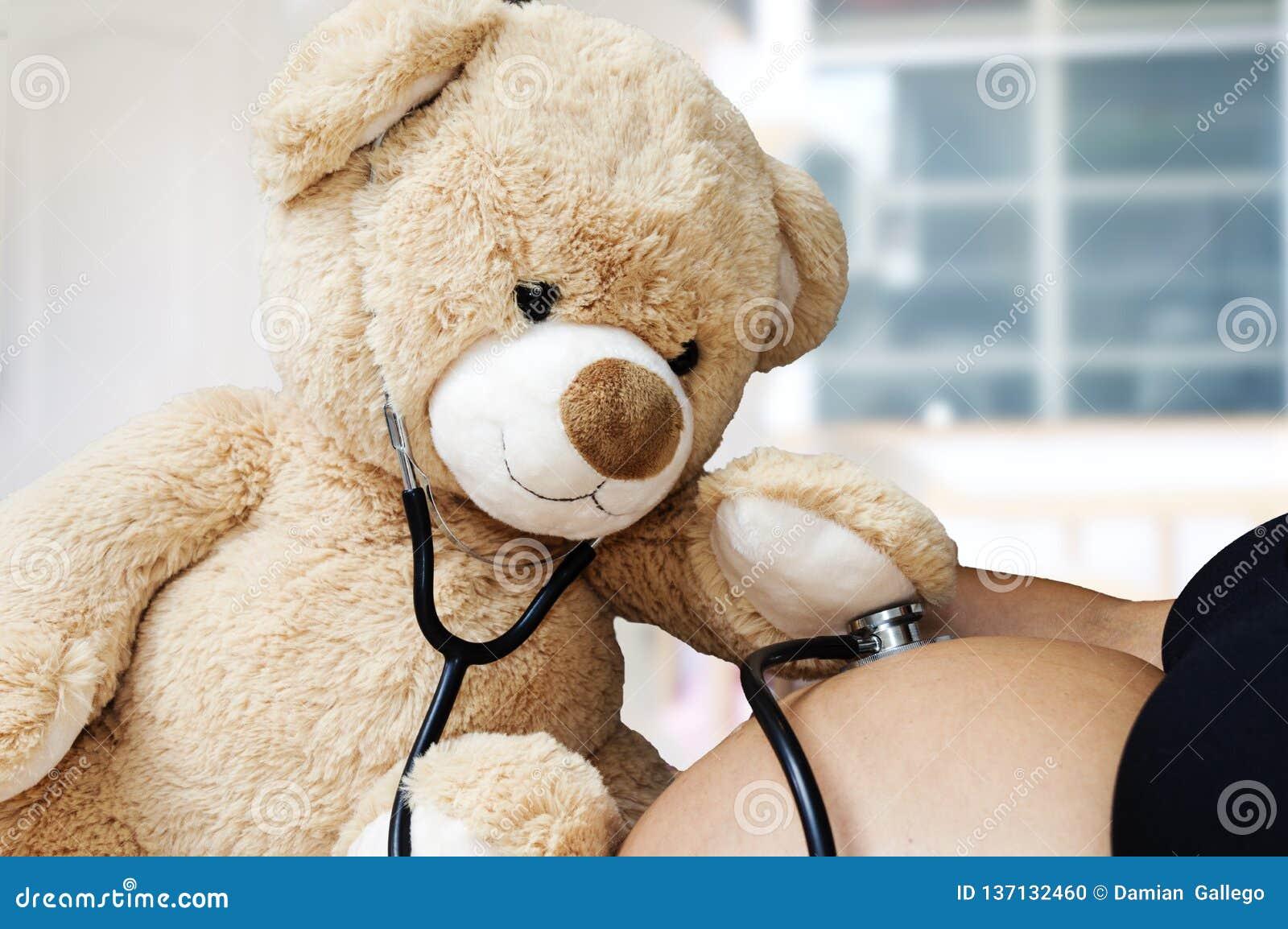 Concepto del embarazo, de la medicina y de la atención sanitaria - ciérrese para arriba del oso de peluche que juega el estetosco
