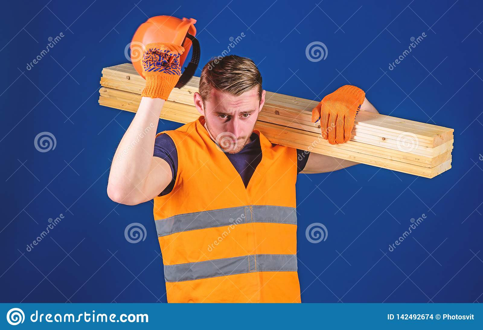 Concepto del equipo protector El hombre en guantes protectores sostiene el visera del casco, corrige el casco en la cabeza, fondo