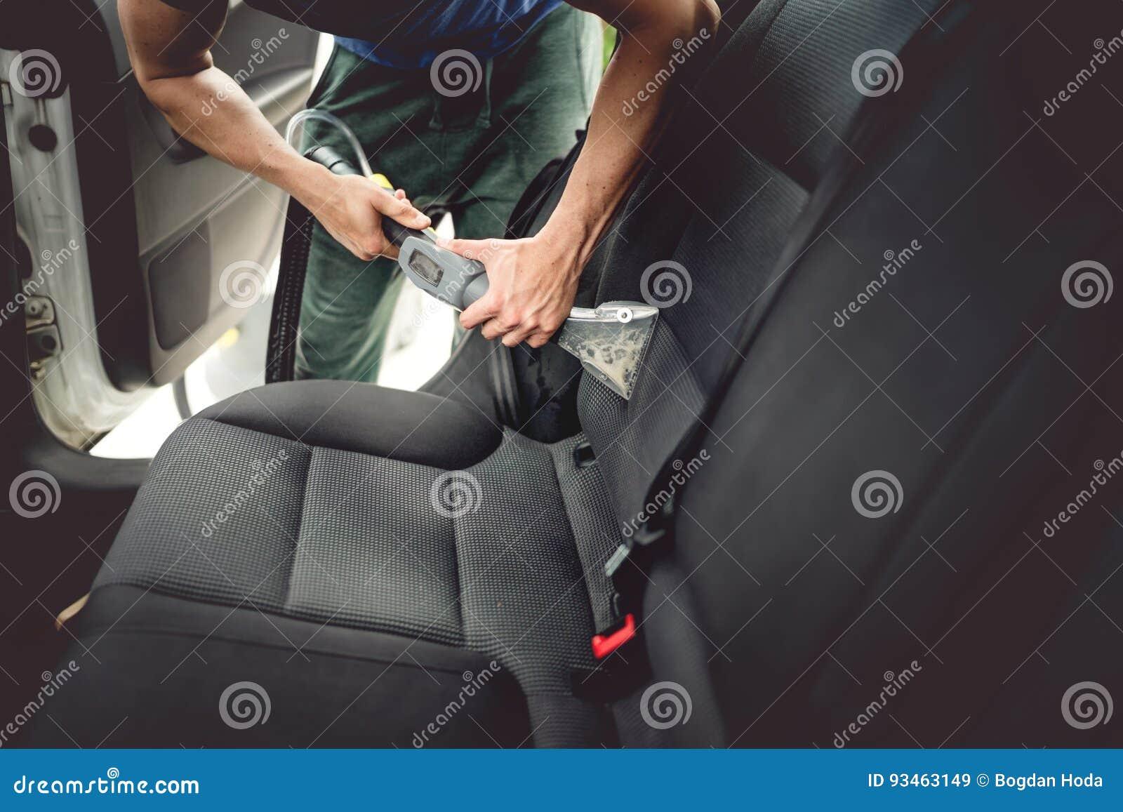 Concepto del mantenimiento del coche, detallando y limpiando de asientos traseros interiores en los coches modernos de lujo