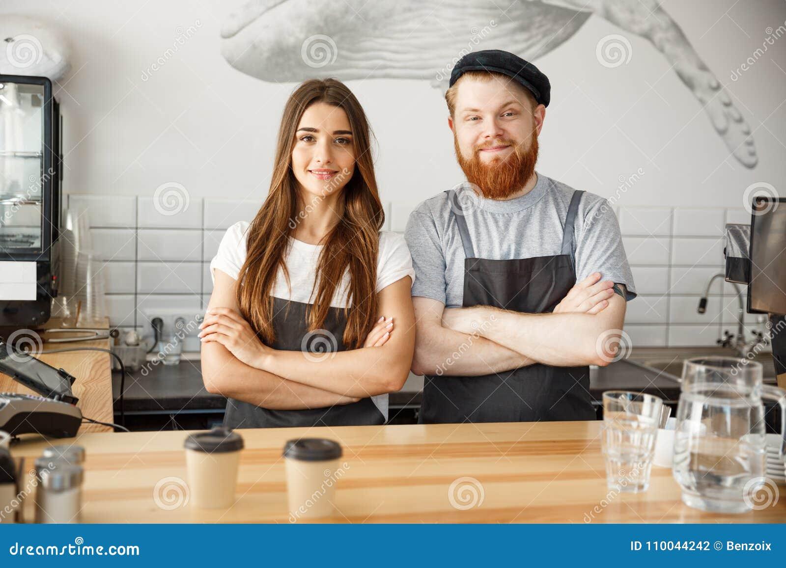 Concepto del negocio del café - hombre barbudo joven positivo y par atractivo hermoso del barista de la señora en el delantal que