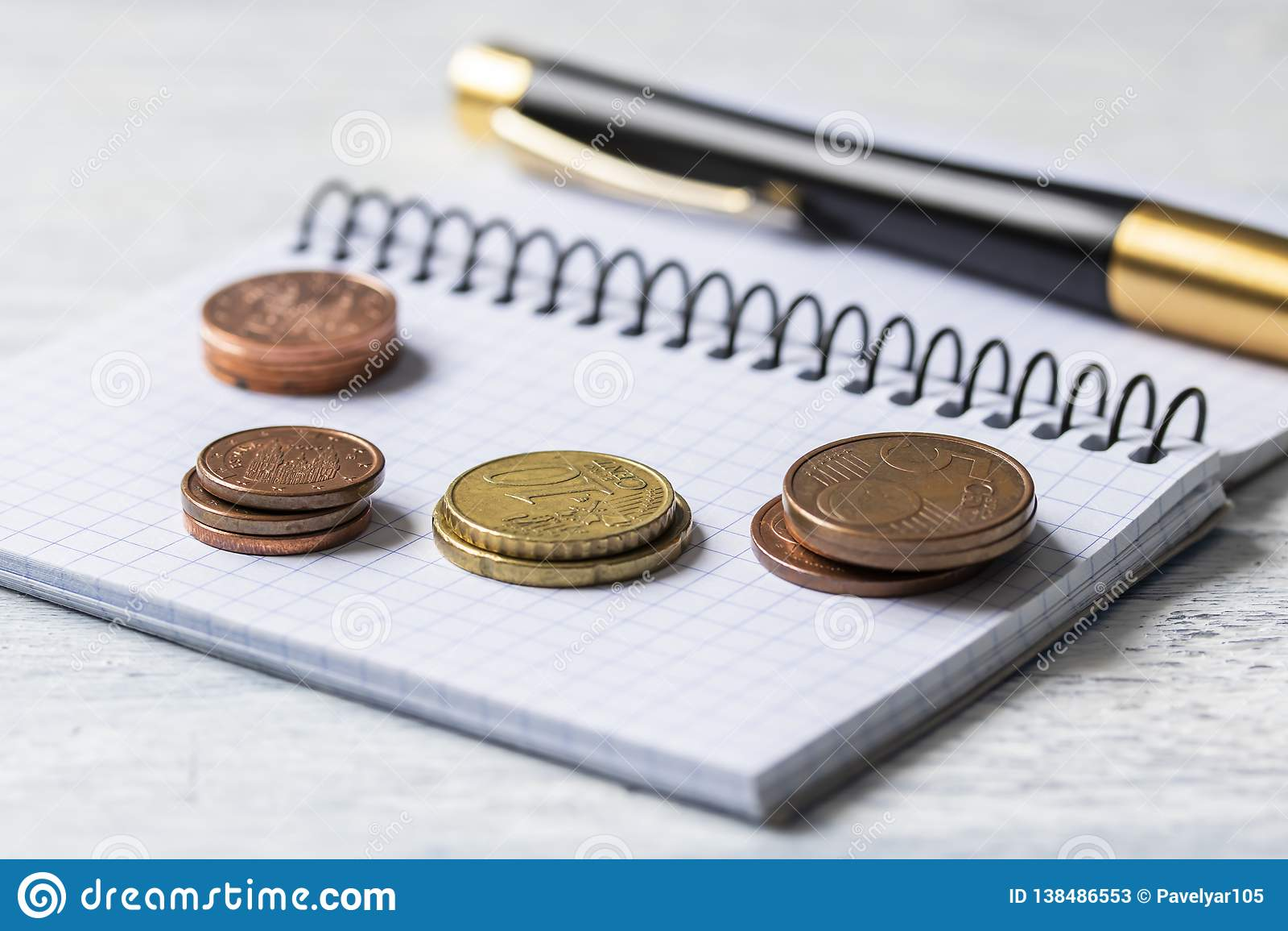 Concepto del negocio, de las finanzas o de la inversión Monedas, talonario de cheques o cuaderno y pluma Fondo de madera blanco