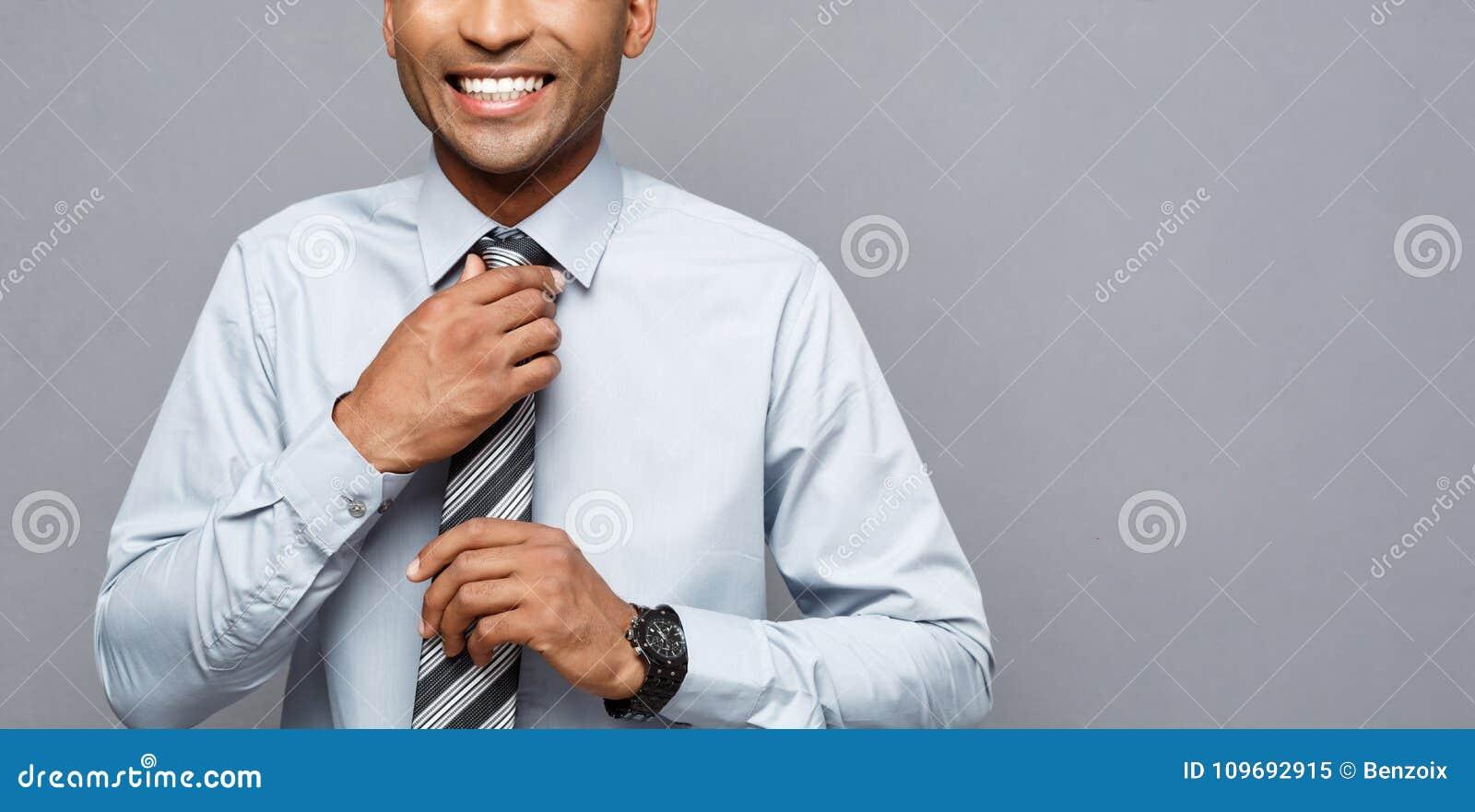 Concepto del negocio - hombre de negocios afroamericano profesional confiado feliz que presenta sobre fondo gris
