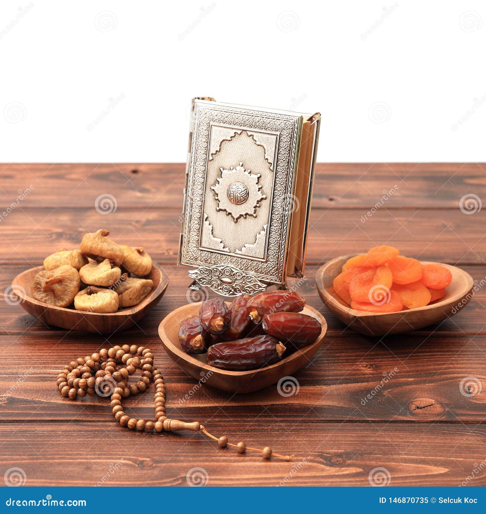 Concepto del partido iftar del Ramad?n Gotas isl?micas del Quran y del rosario del libro sagrado con las fechas deliciosas, higos