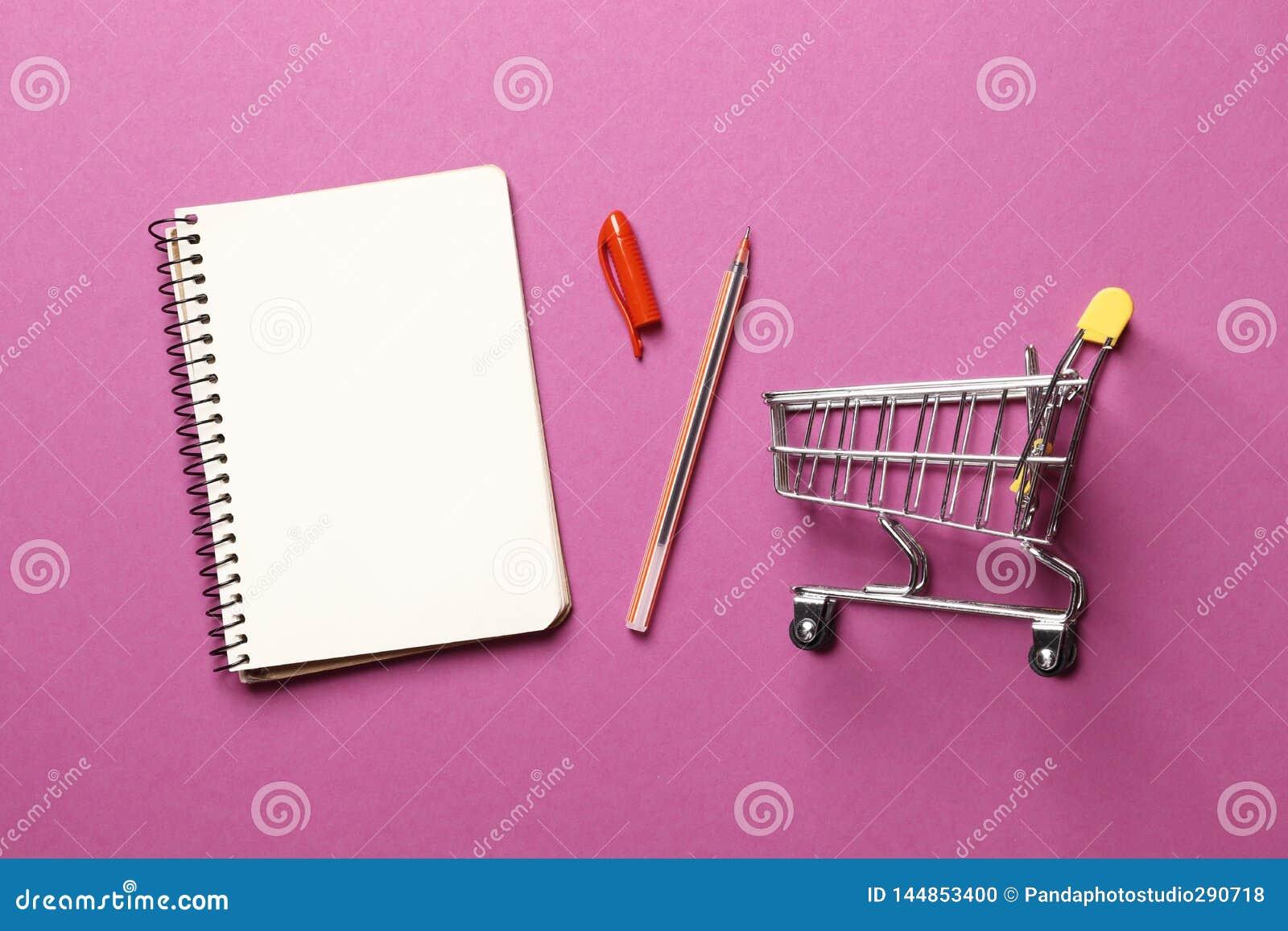 Concepto del presupuesto carro de la compra, cuaderno de papel en blanco