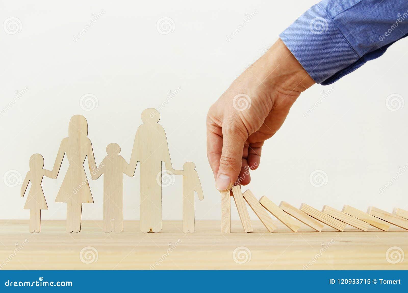 Concepto del seguro Hombre de negocios que protege a una familia contra efecto de dominó vida, financiero y problemas de salud