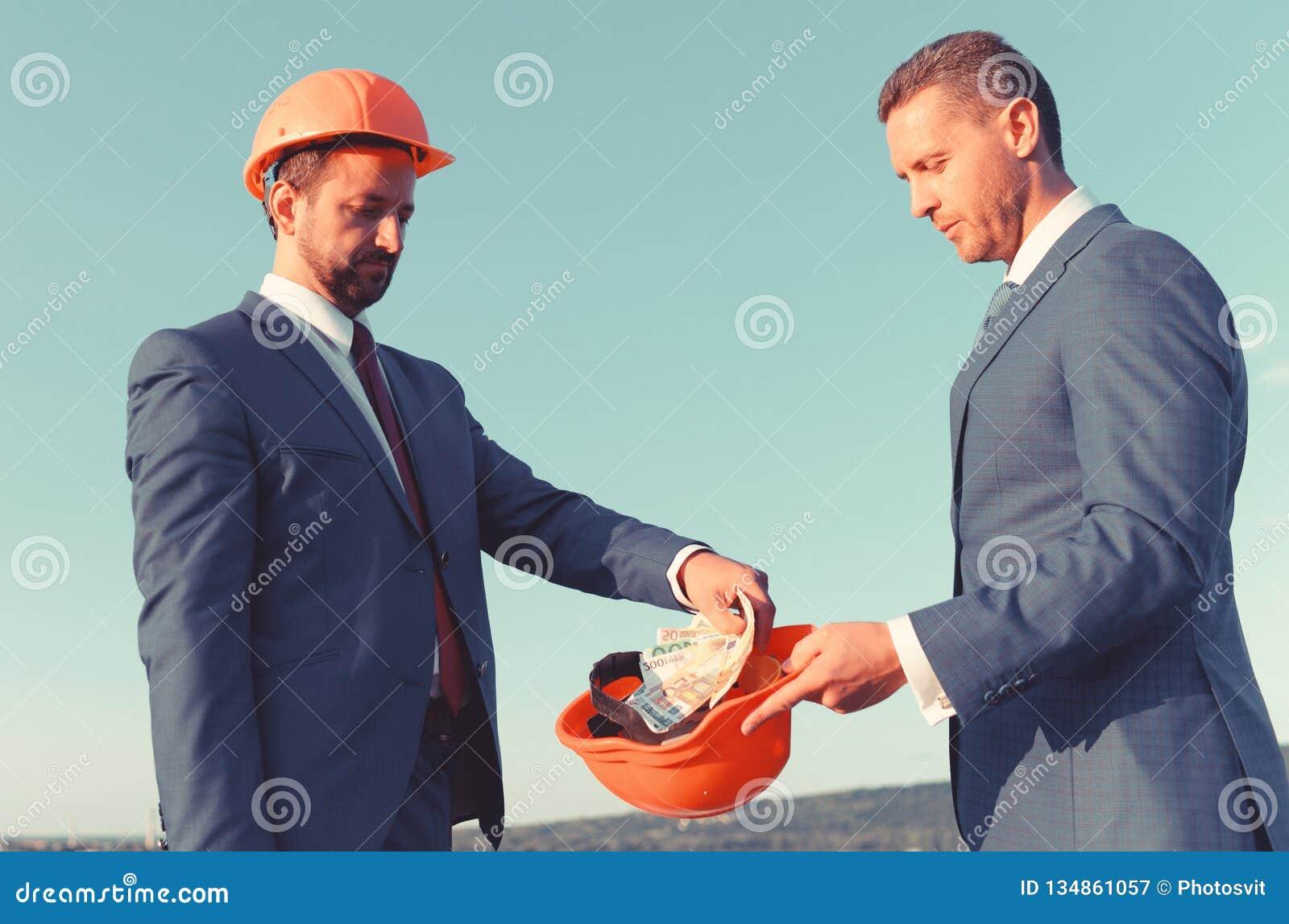 Concepto del soborno y del negocio del negocio Arquitectos con las caras serias