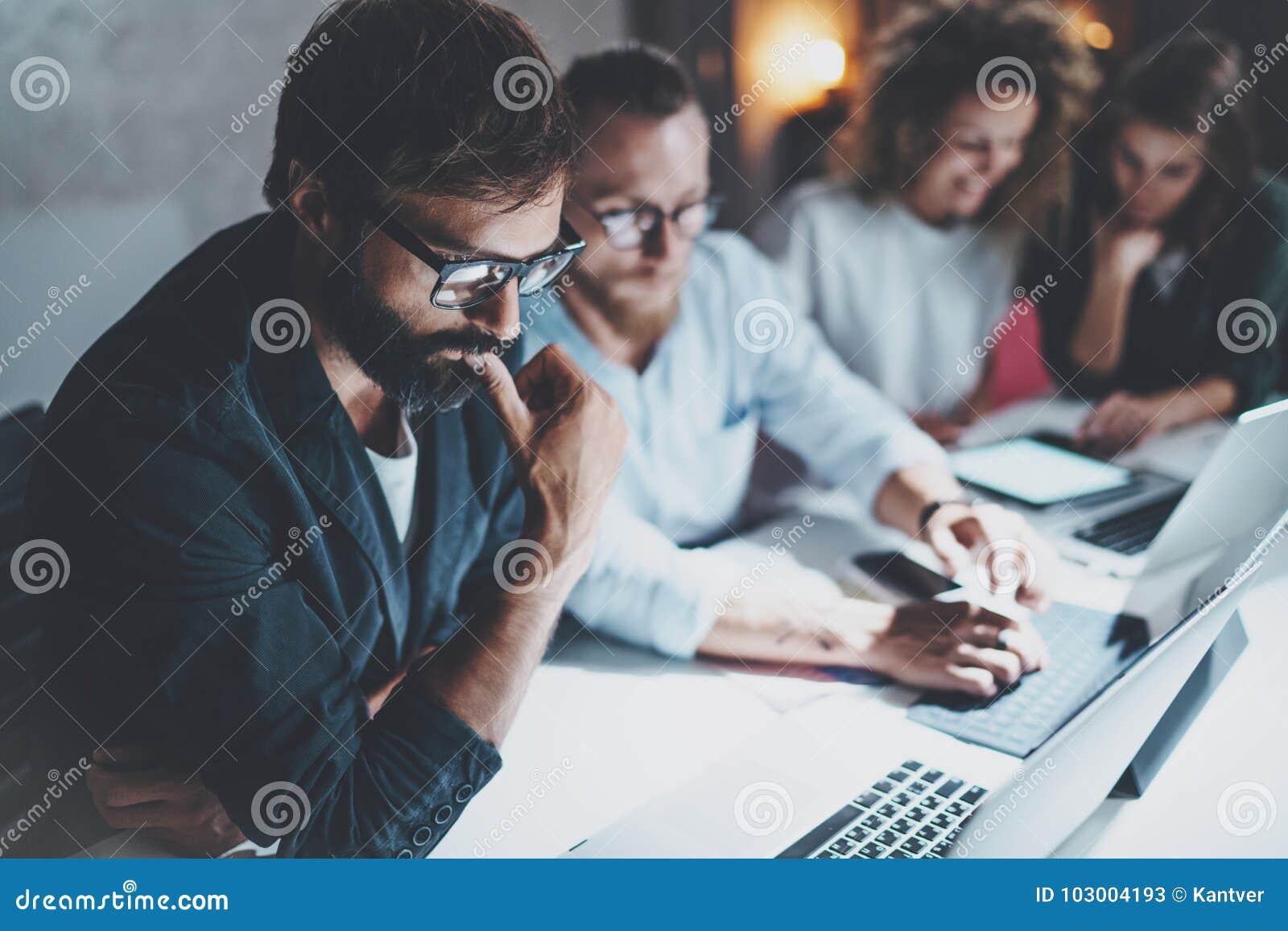 Concepto del trabajo en equipo Equipo de proyecto que hace la conversación en la sala de reunión en la oficina de la noche Gente