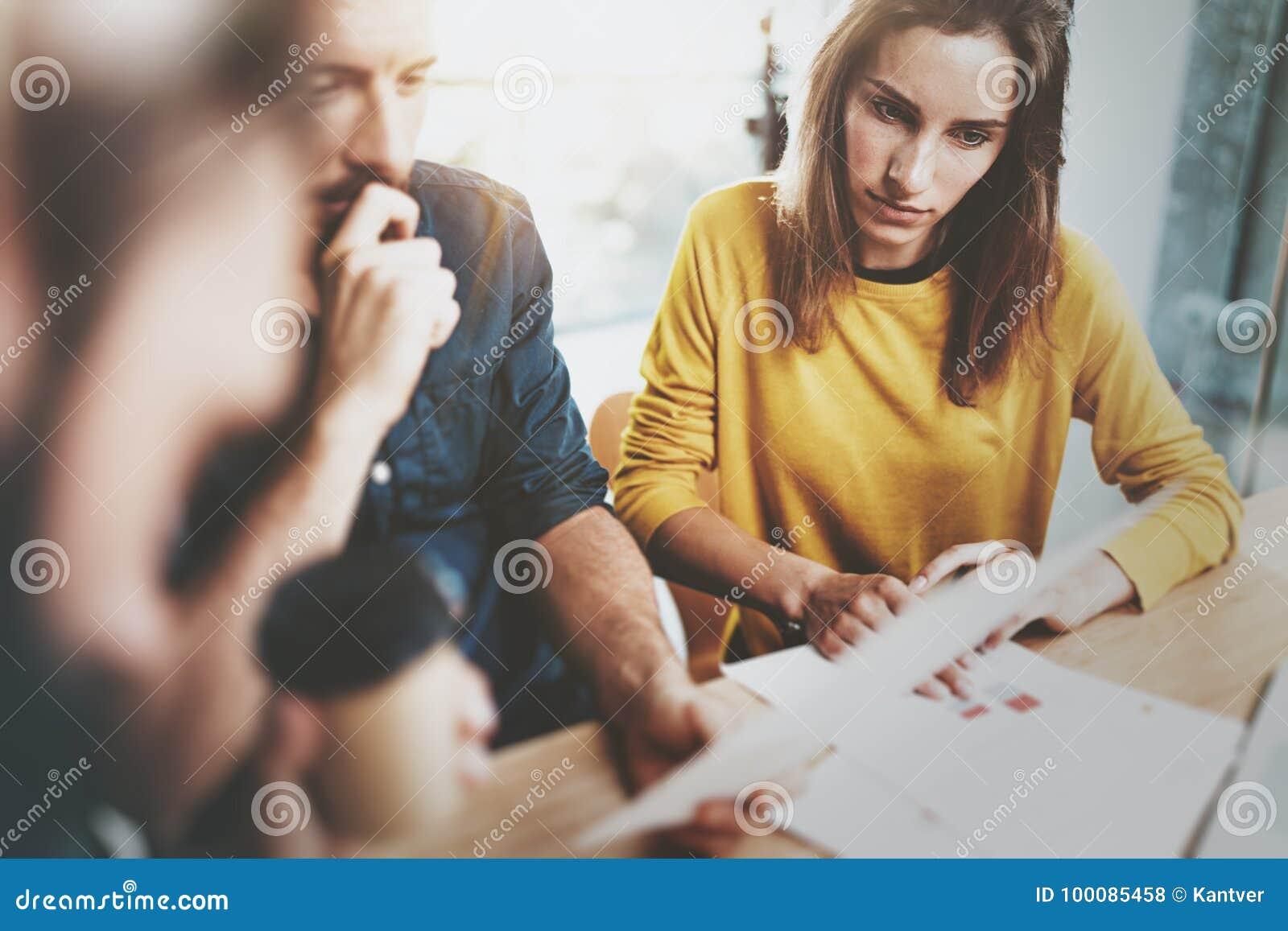Concepto del trabajo en equipo Proceso de Coworking en la oficina soleada del desván Equipo del negocio que hace la conversación