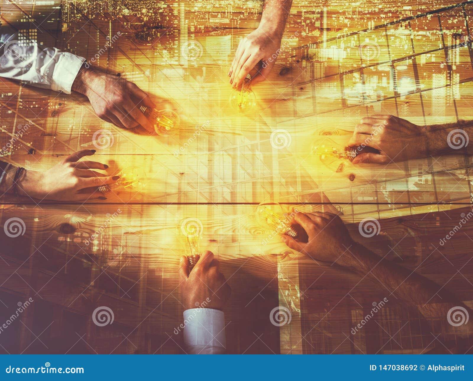 Concepto del trabajo en equipo y de la reuni?n de reflexi?n con los hombres de negocios que comparten una idea con una l?mpara In