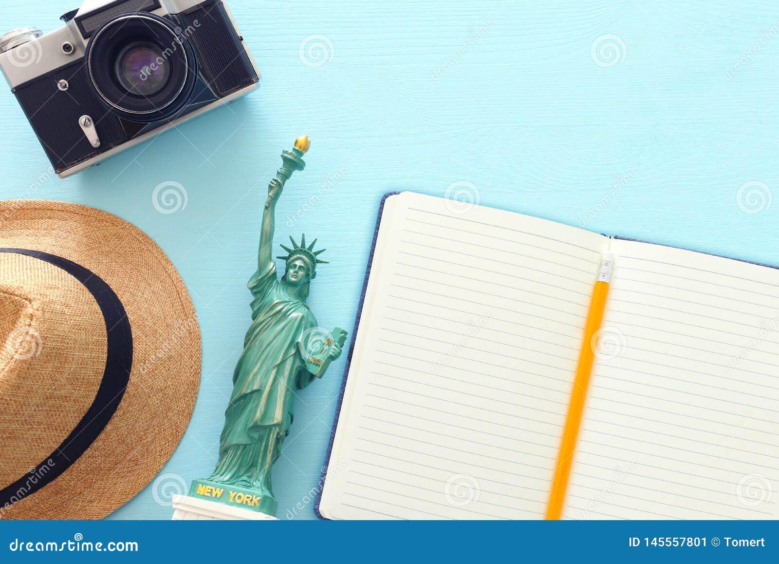 Concepto del viaje con la estatua americana del s?mbolo de la libertad y el cuaderno en blanco para el contexto