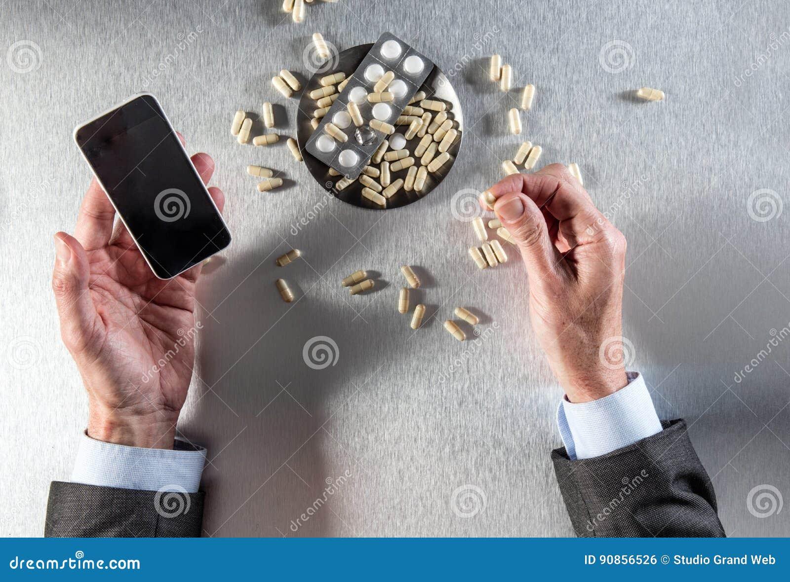 Concepto en línea de la farmacia - el hombre de negocios da sostener el teléfono a las drogas de la orden