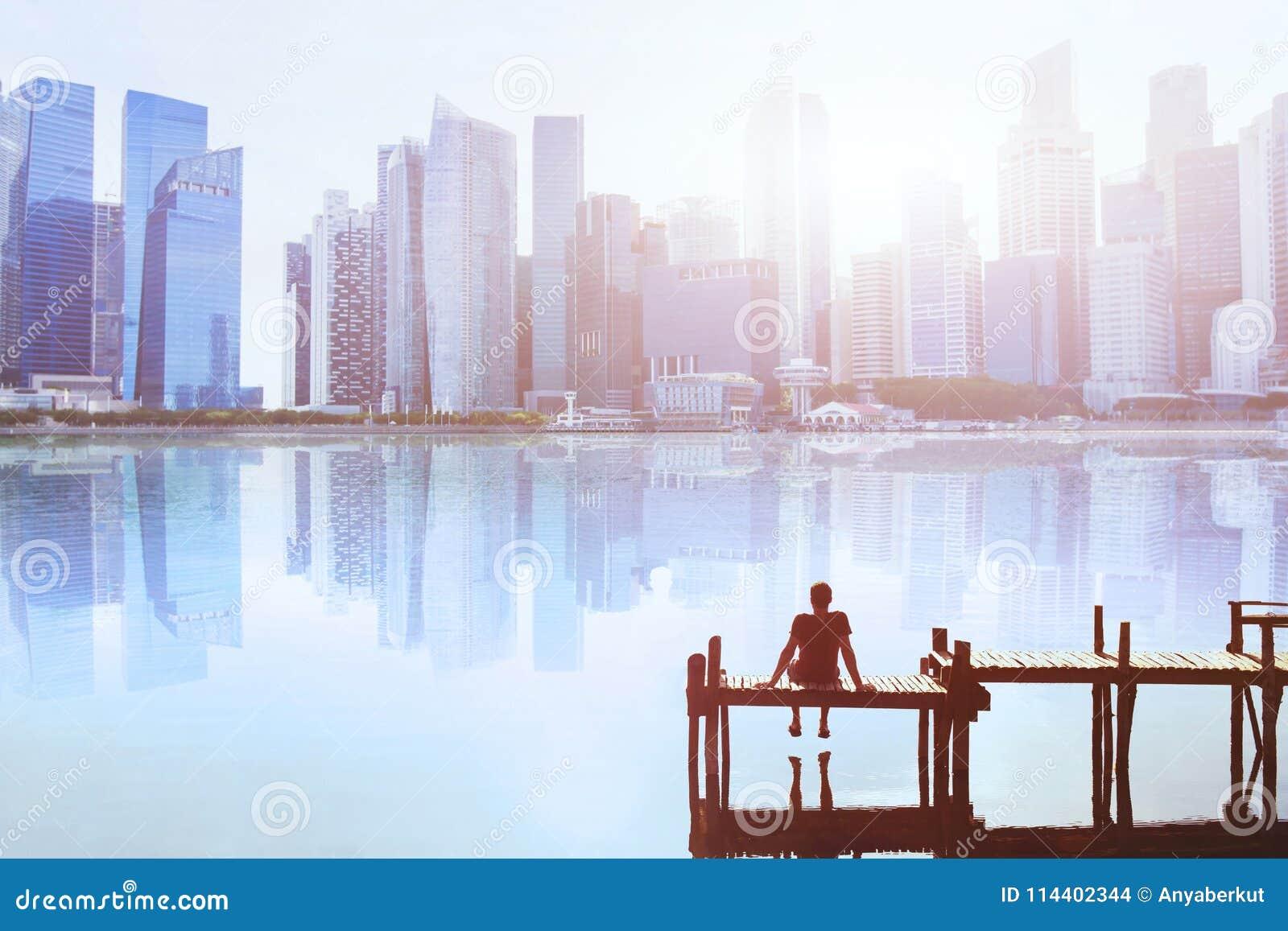 Concepto ideal, hombre que se sienta en el embarcadero y que disfruta de paisaje urbano moderno