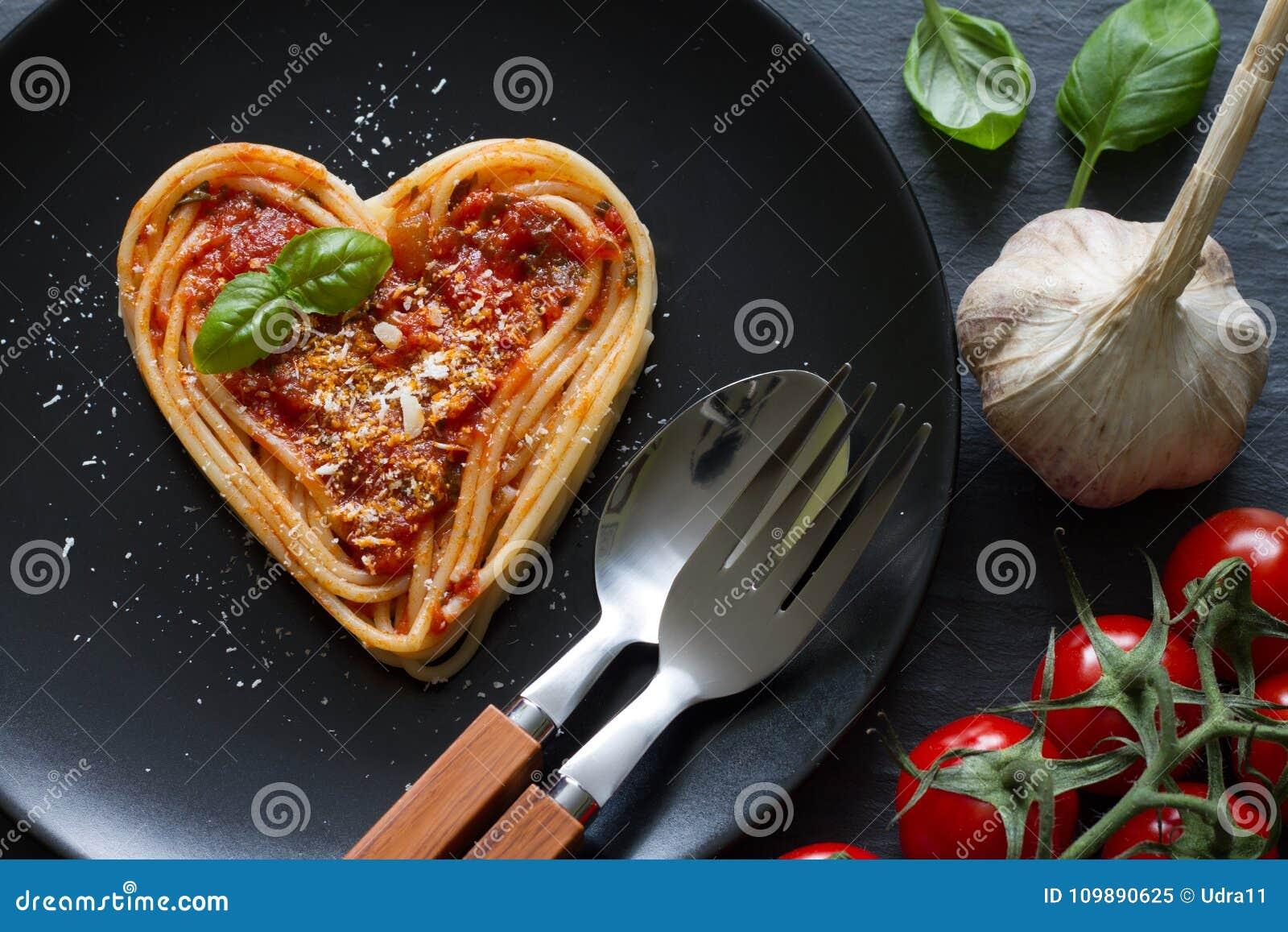 Concepto italiano del extracto de la dieta del amor del corazón de las pastas de los espaguetis en fondo negro
