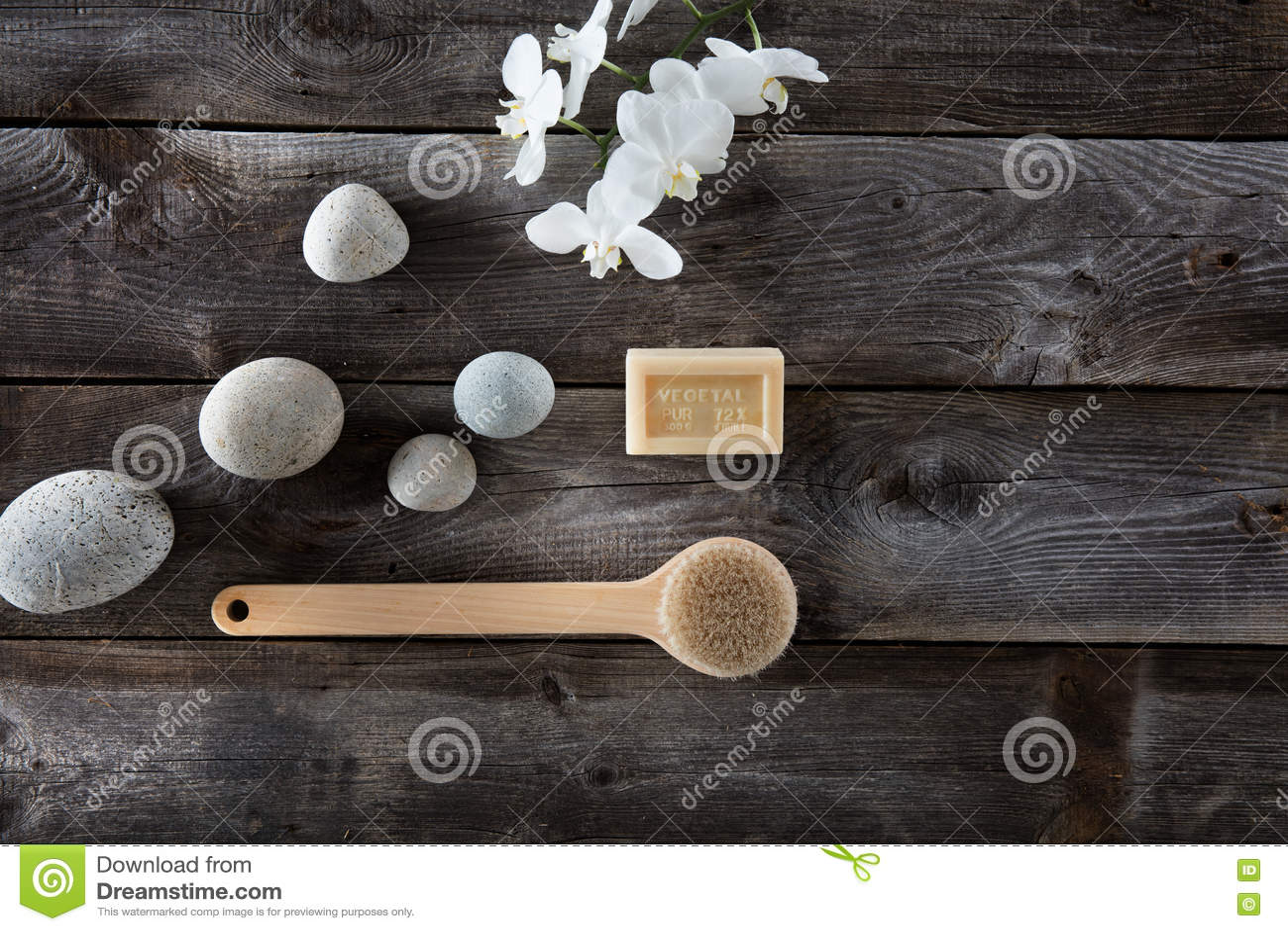 Concepto natural del baño con los guijarros, el cepillo de la parte posterior y las orquídeas blancas