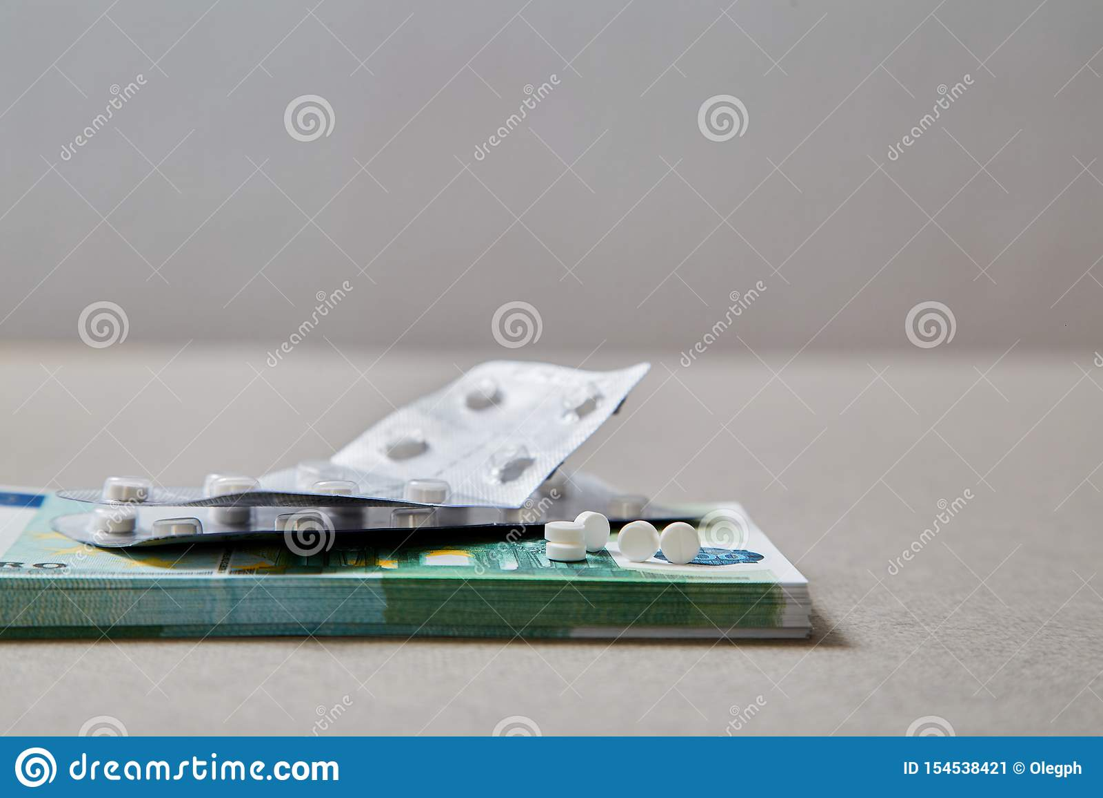 Concepto para la medicina costosa de la atención sanitaria, farmacéutica y pagada Tabletas que mienten en un paquete de billetes
