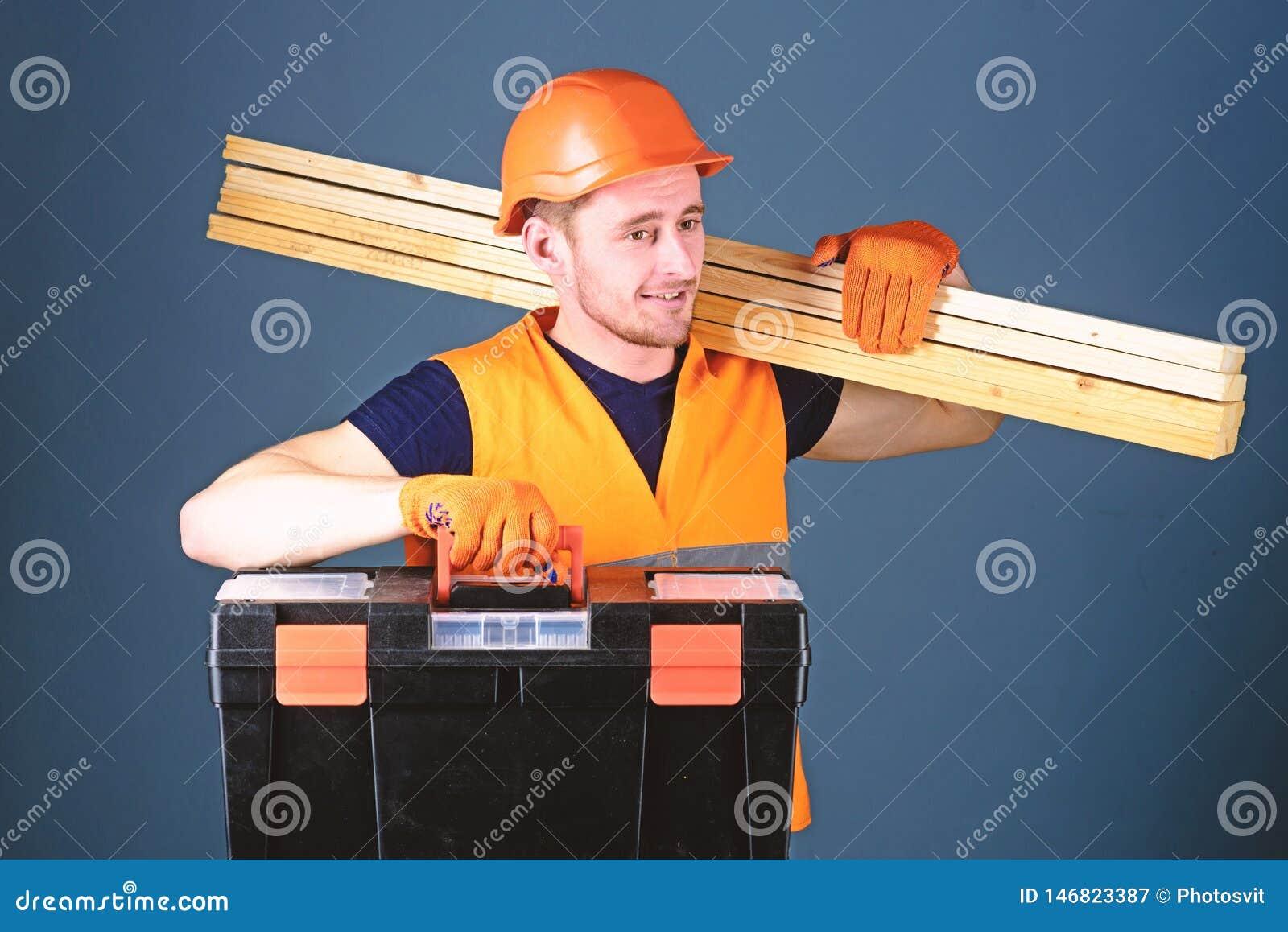Concepto profesional del carpintero El carpintero, trabajador, constructor, carpintero en cara sonriente lleva haces de madera en