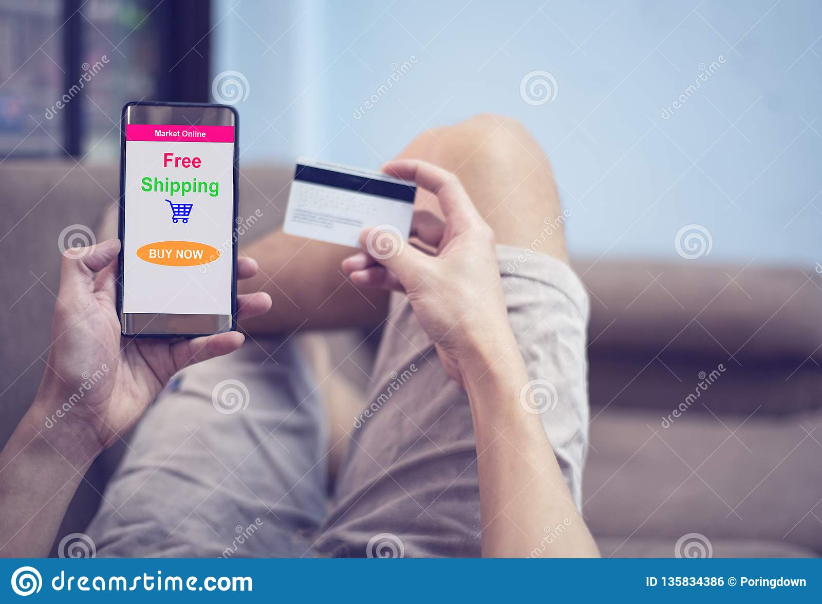 Concepto que hace compras en línea - hombre joven usando compras del smartphone en mercado de la página web en línea y manos que