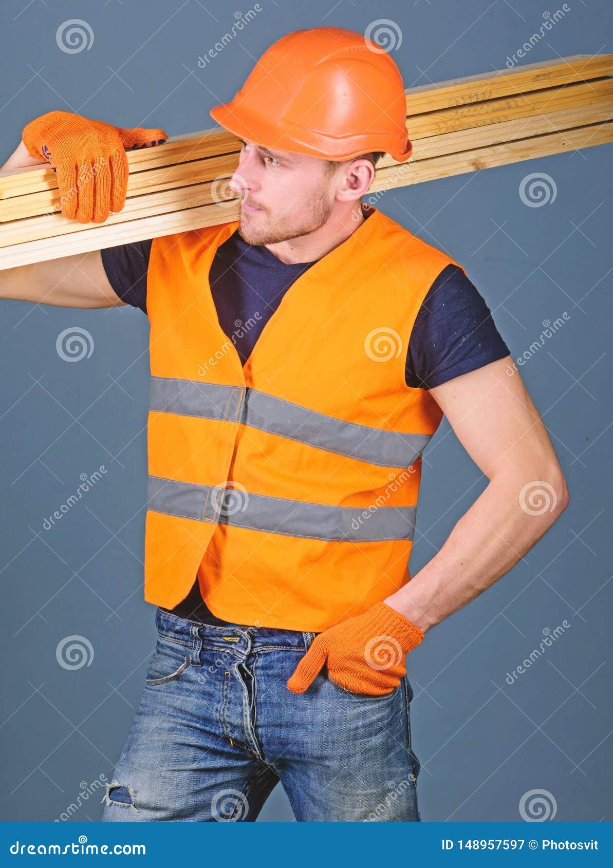 Concepto resistente del trabajador El carpintero, carpintero, trabajador, constructor en cara ocupada lleva haces de madera en ho