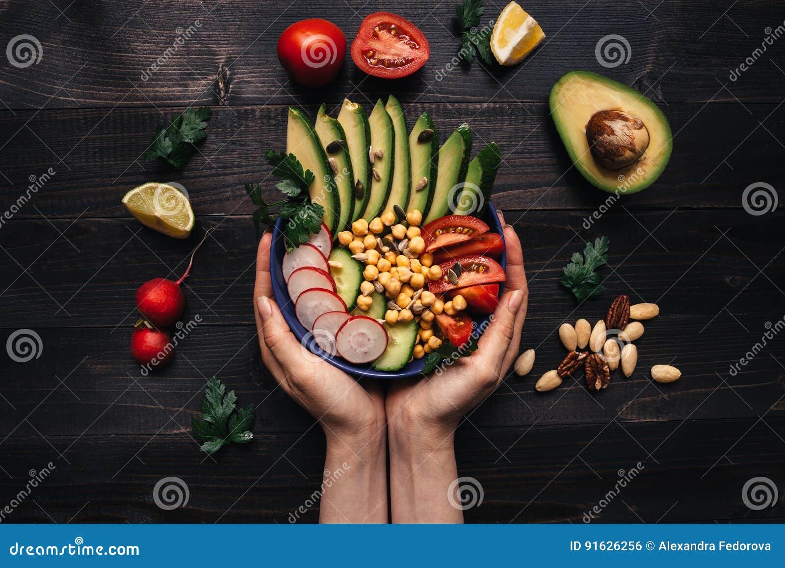 Concepto sano del alimento Manos que sostienen la ensalada sana con el garbanzo y las verduras Comida del vegano Dieta vegetarian