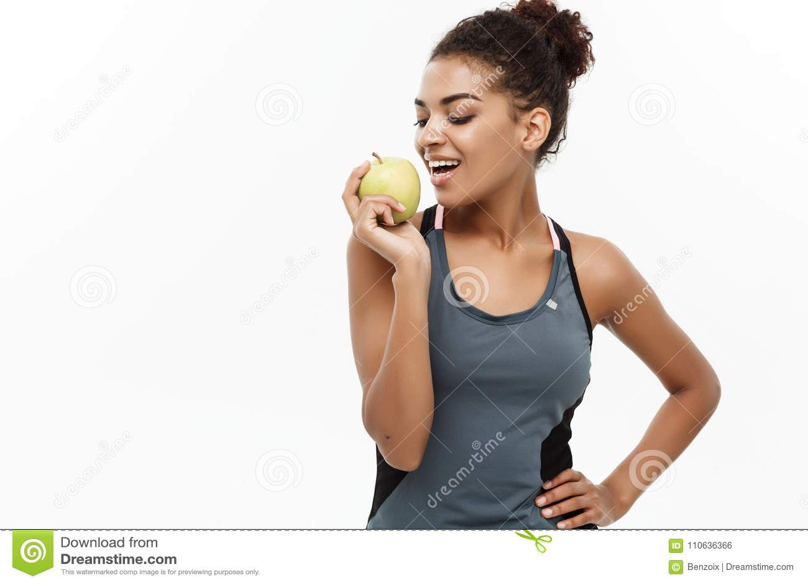 Concepto sano y de la aptitud - la señora africana americana hermosa en aptitud gris viste la consumición de la manzana verde ais