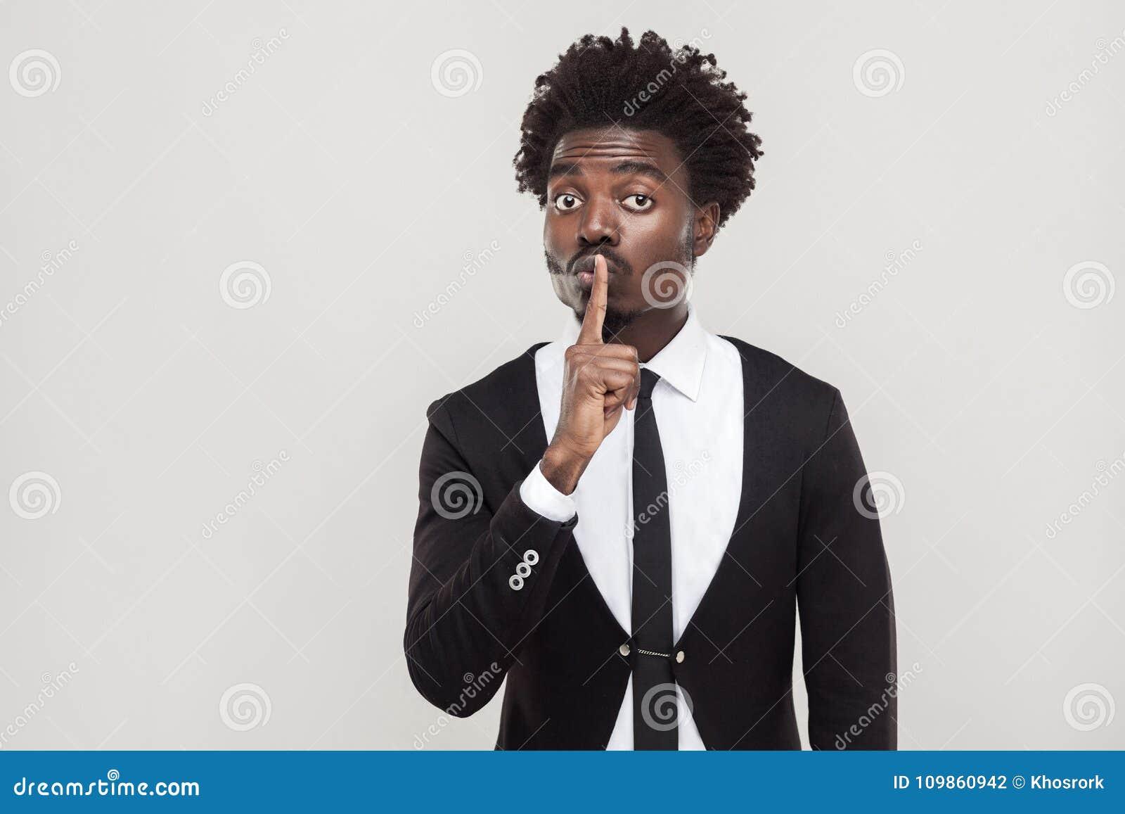 Concepto secreto o reservado Hombre de negocios africano que muestra shh la muestra en