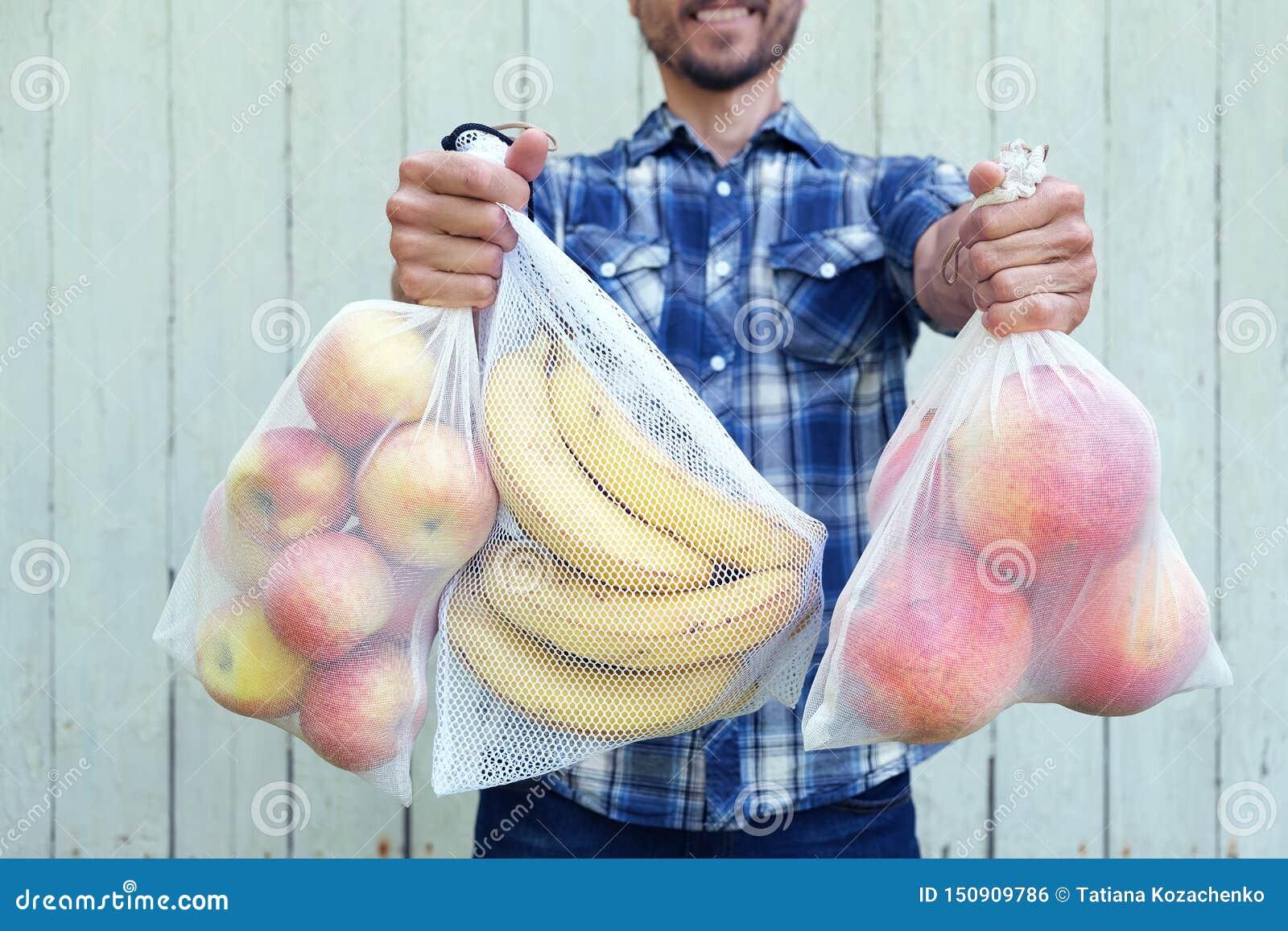 Concepto in?til cero de las compras Hombre sonriente que sostiene bolsos reutilizables del eco con las frutas frescas Pl?stico no