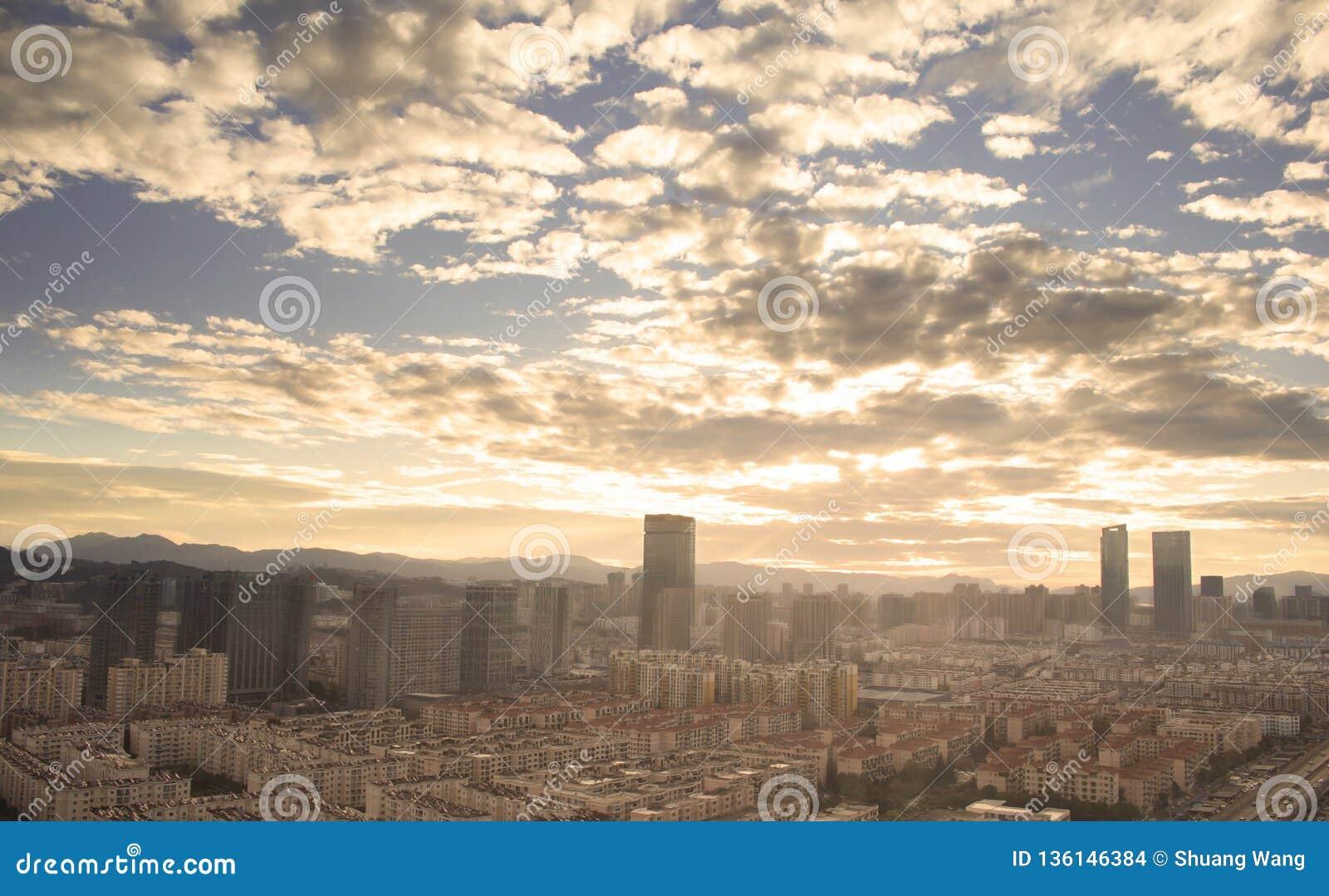 Concepto urbano de las propiedades inmobiliarias: ciudad en el cielo del color y el fondo crepusculares del paisaje urbano de las