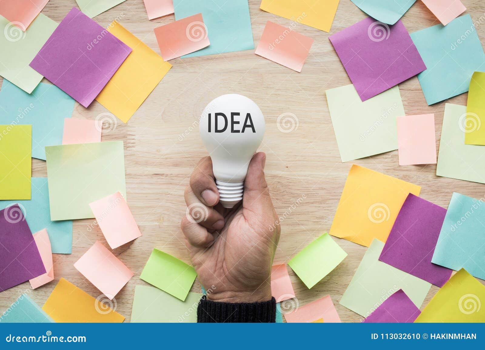 Conceptos de las ideas de la inspiración con la mano que sostiene la bombilla blanca