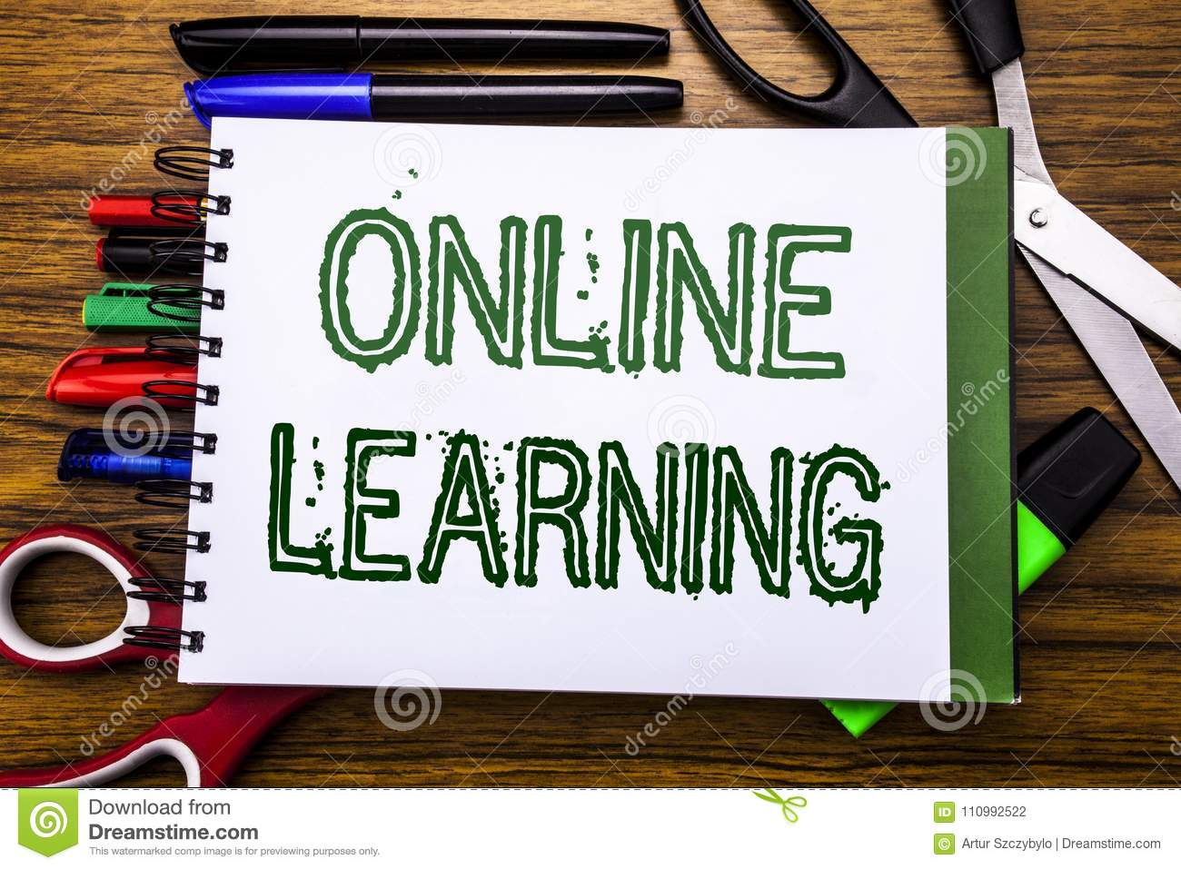 Conceptual hand writing text Online Learning. Concept for E-learning Training Written on notebook, wooden background with office