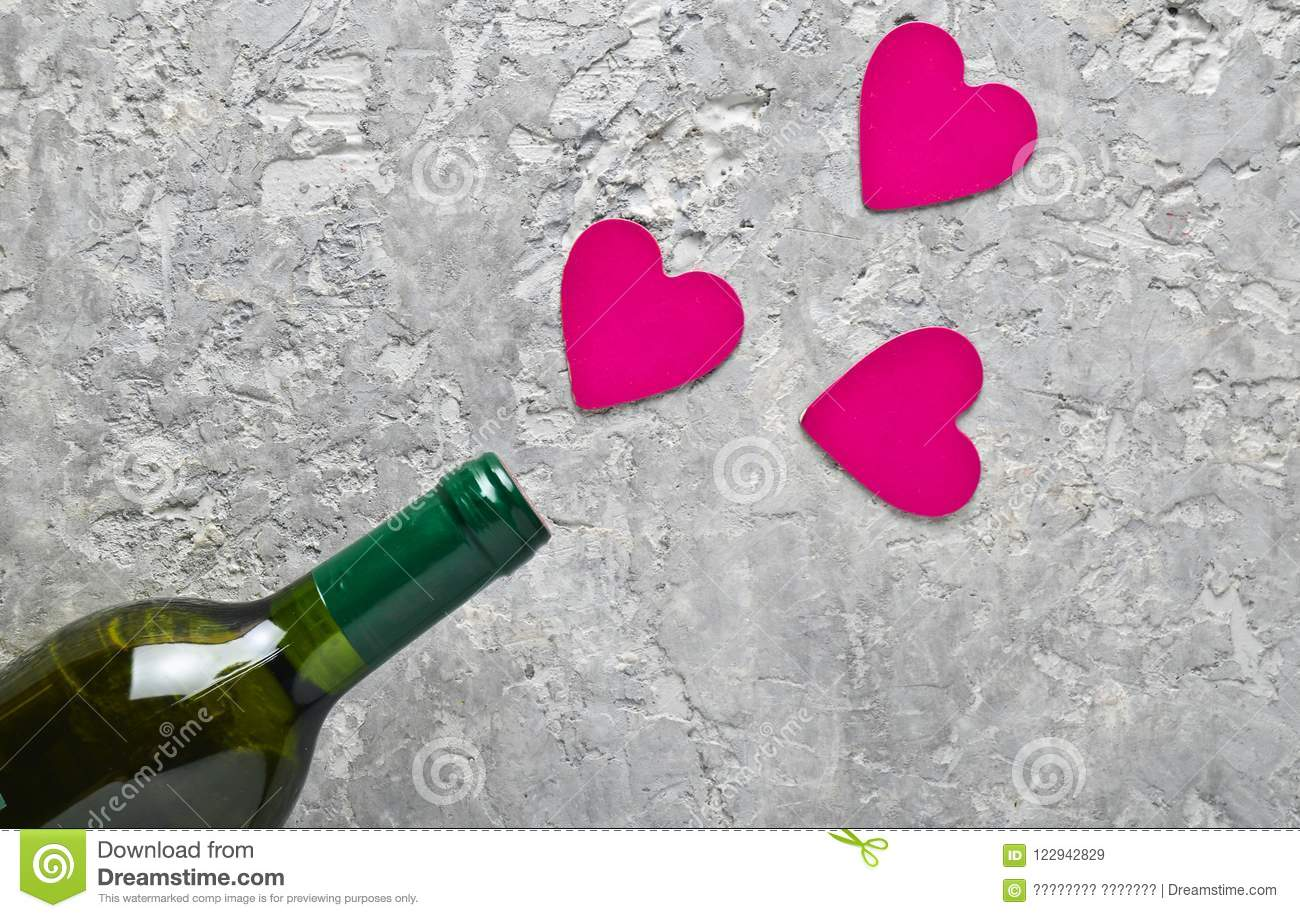 Conceptual photo Bottles of wine and pink decorative hearts. Love, romantic concept, top view.